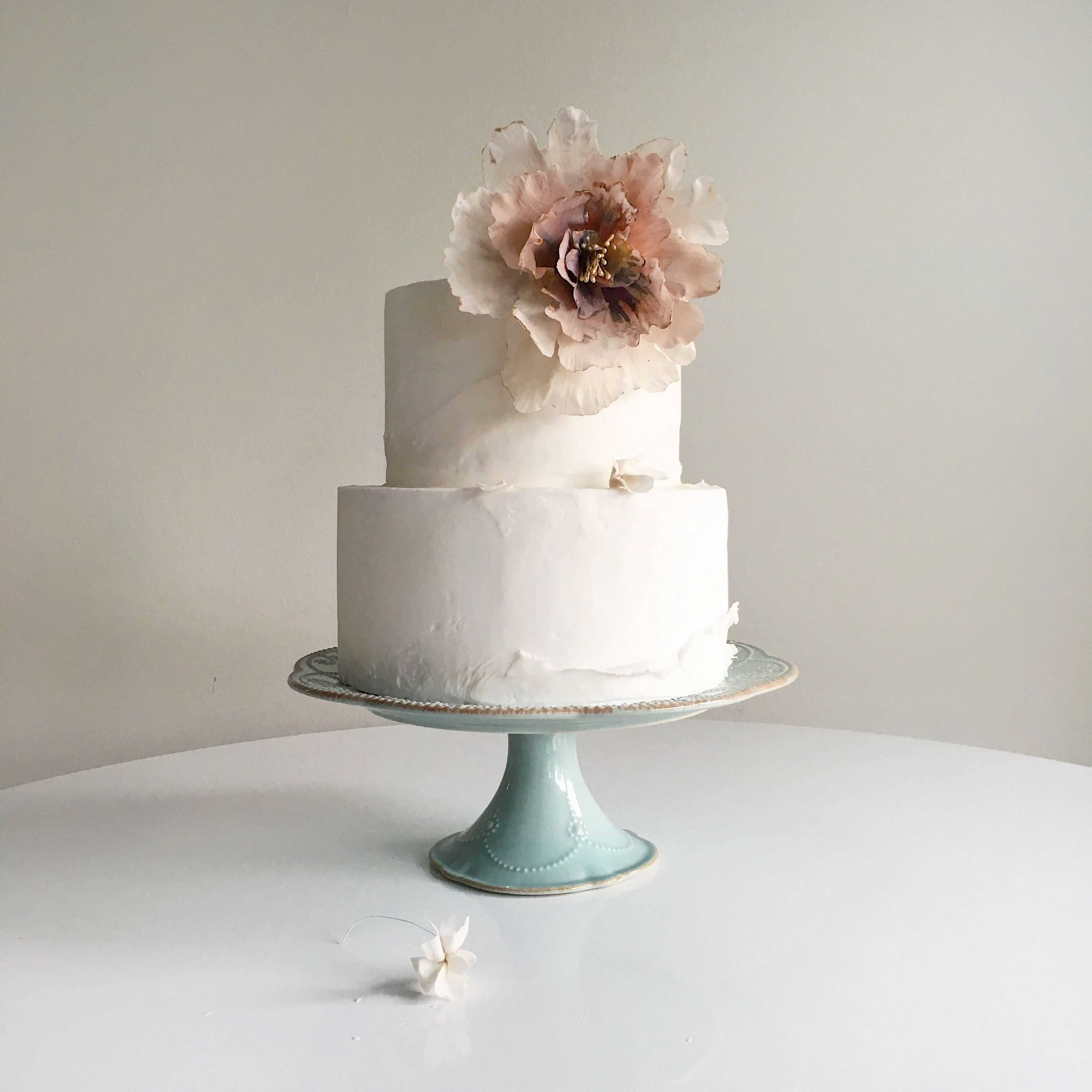 Ivory torn fondant wedding cake with sugar flower