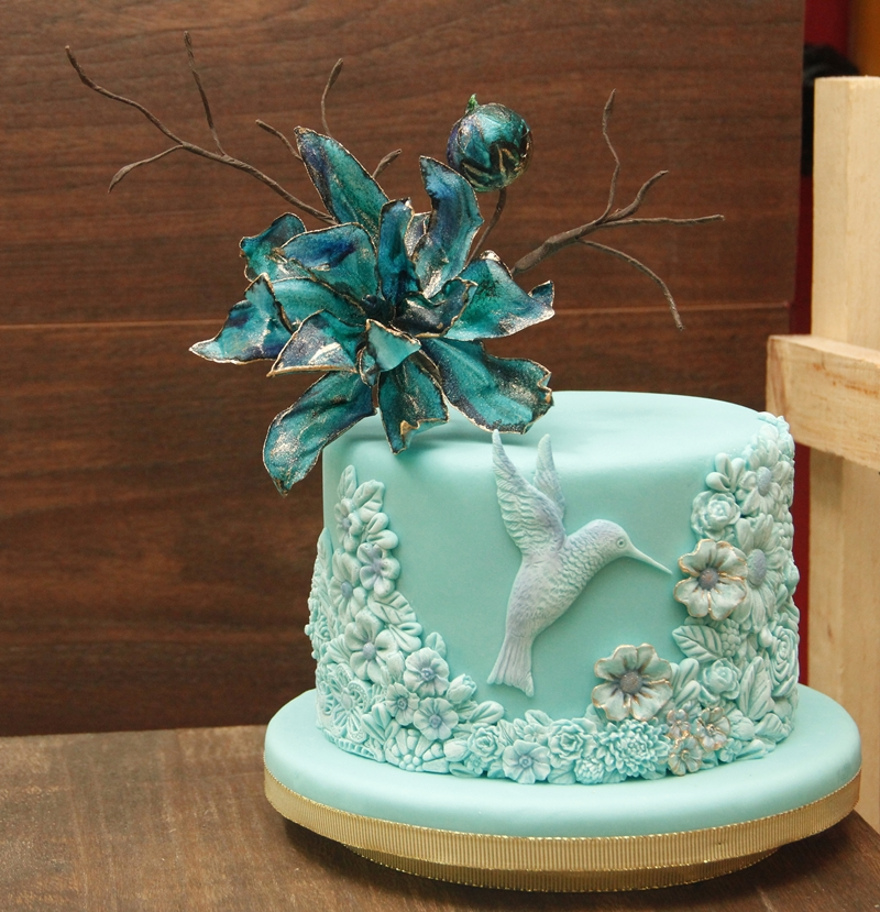 Turquoise hummingbird cake with sugar flower