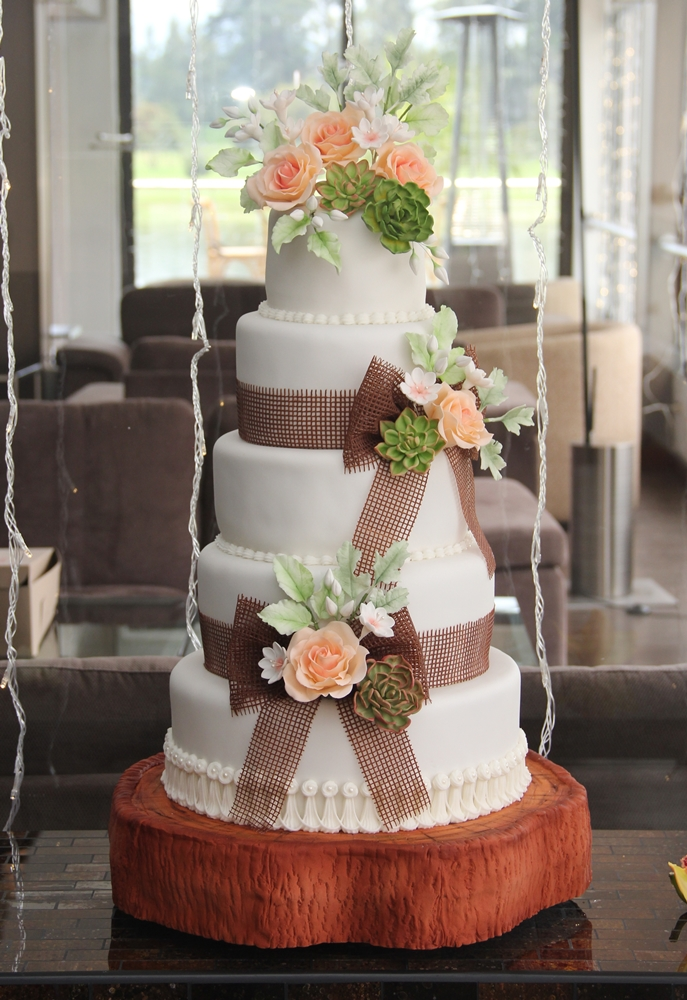 White wedding cake with burlap and sugar flowers