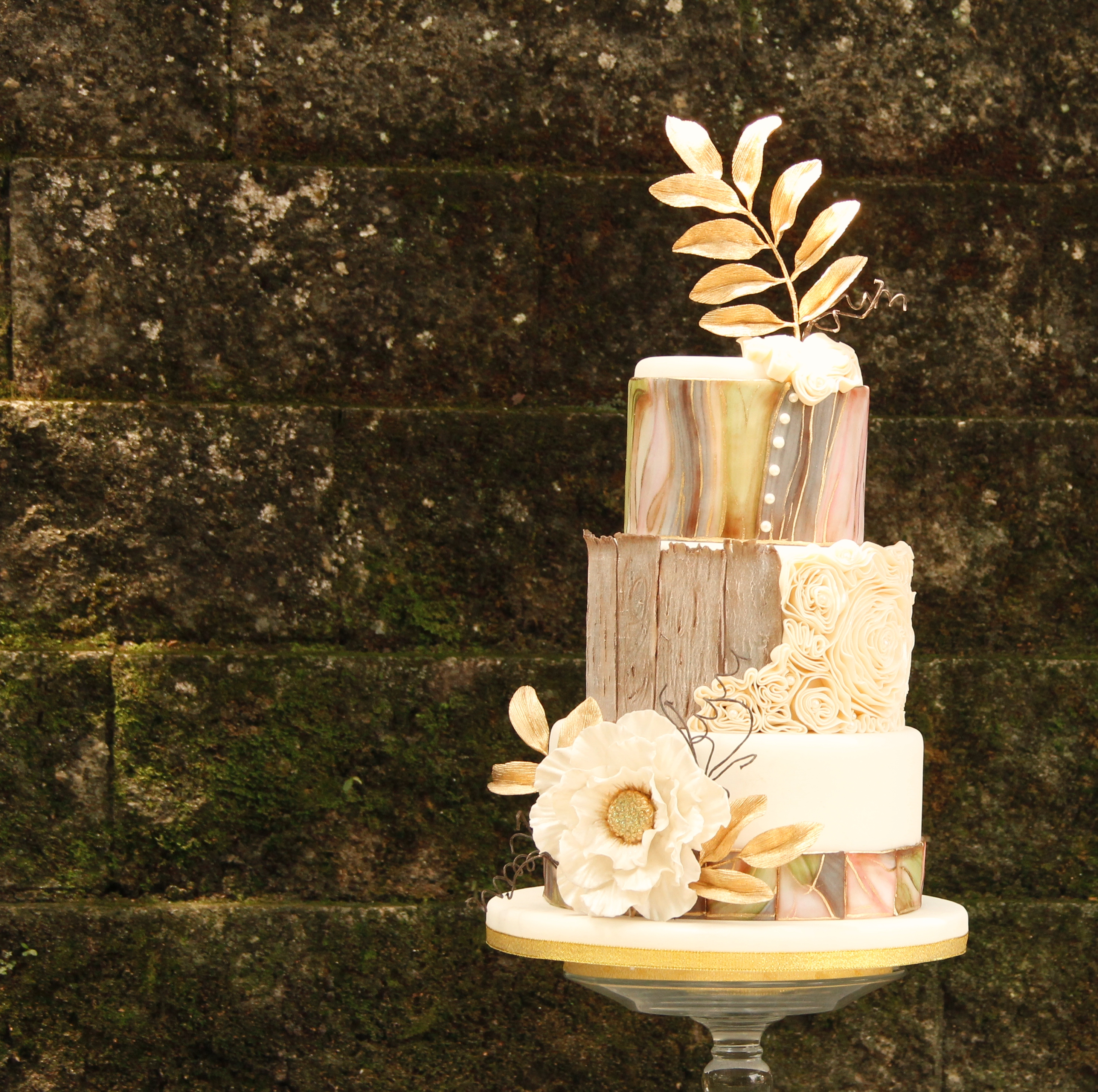 Gray and ivory exposed bark wedding cake with gold leaf