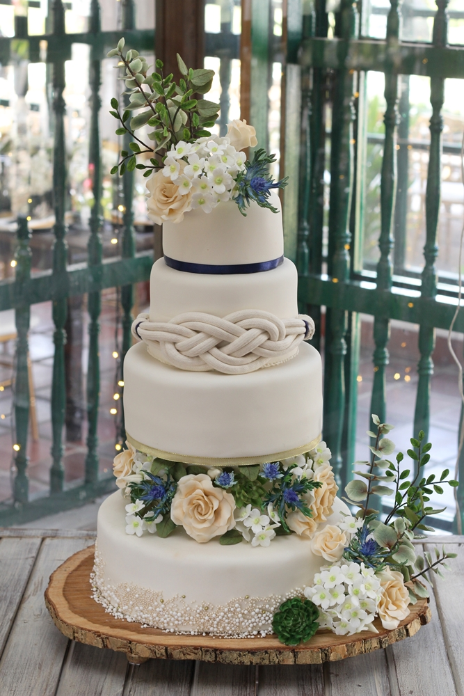 White wedding cake with rope and sugar flowers
