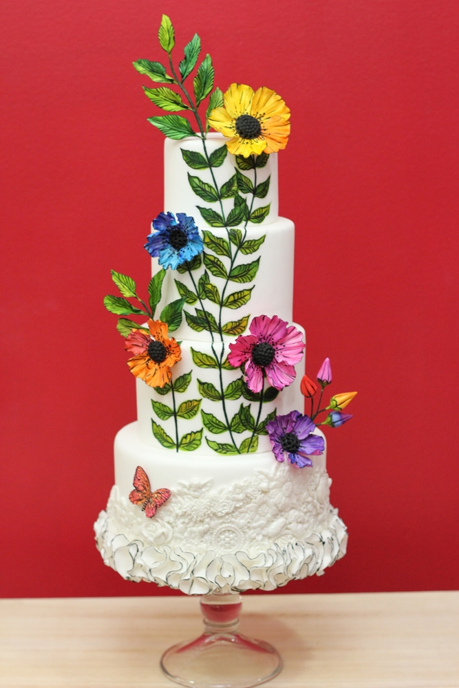White bas relief cake with bright sugar flowers