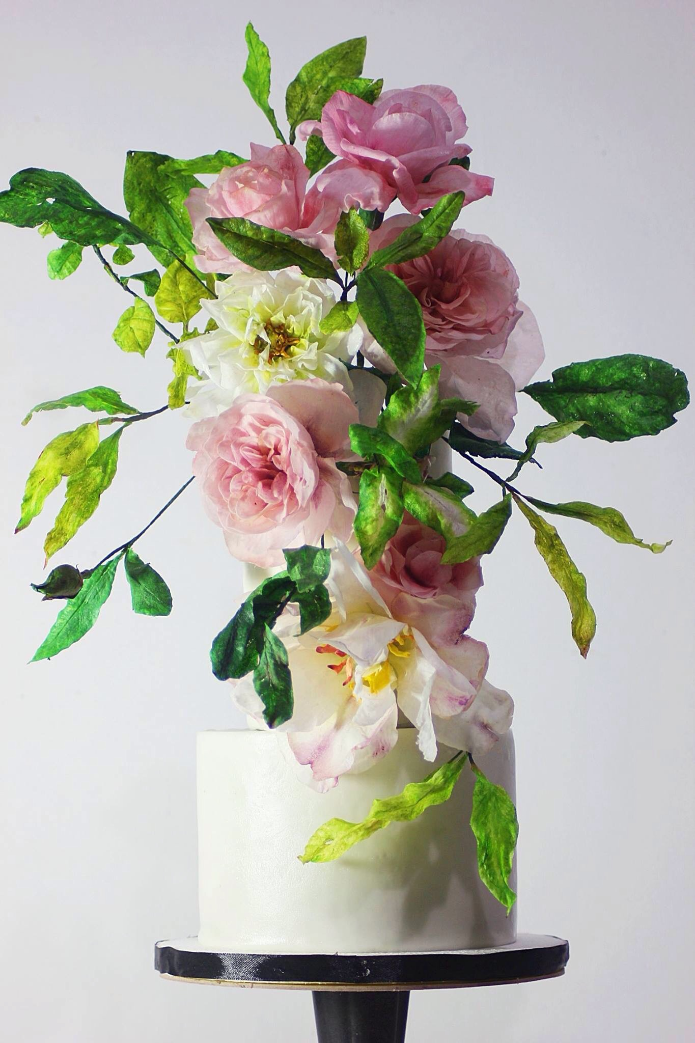 White wedding cake with cascading pink sugar flowers
