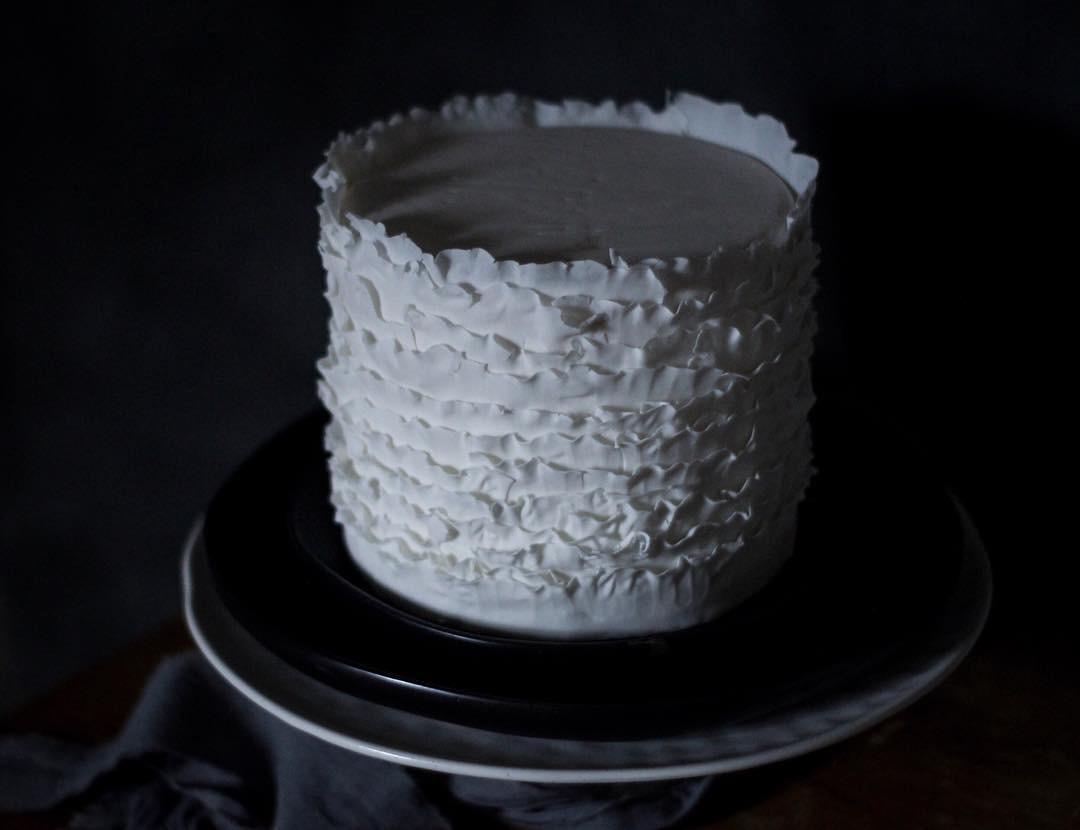 White fondant tiered ruffle barrel cake