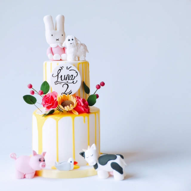 White and yellow birthday drip cake with animal toppers