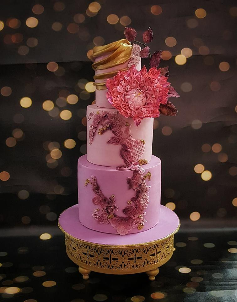Shades pink fondant wedding cake with gold trim and texture