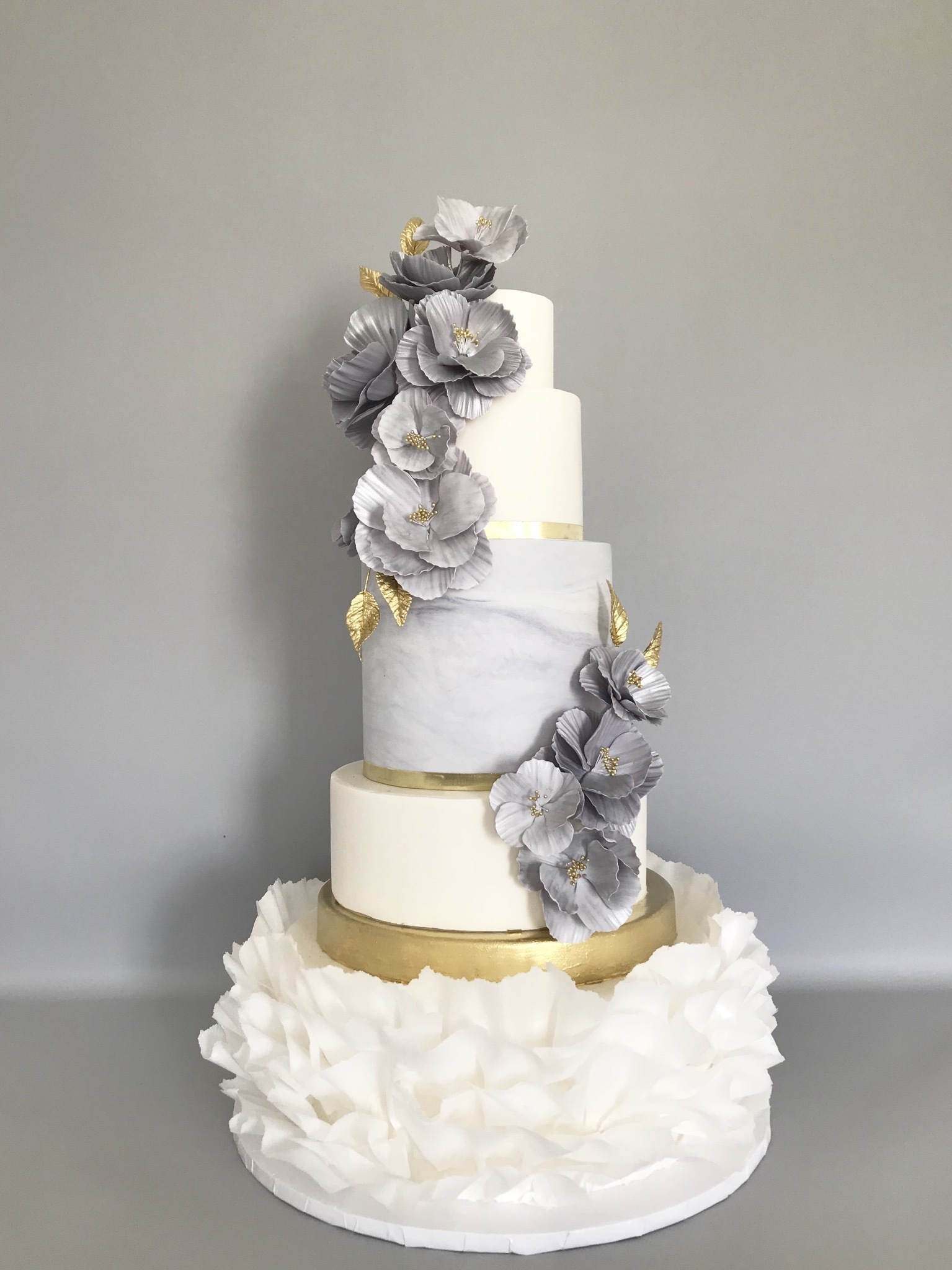 White and marbled gray fondant wedding cake with ruffles
