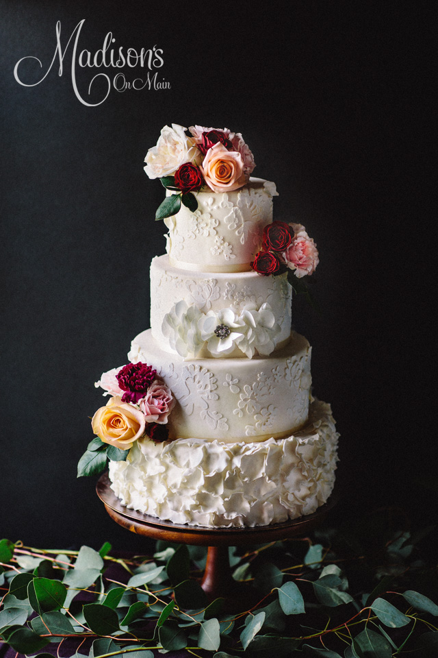 White lace and textured ruffle wedding cake with sugar flowers