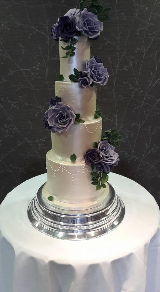 Silver wedding cake with purple sugar flowers