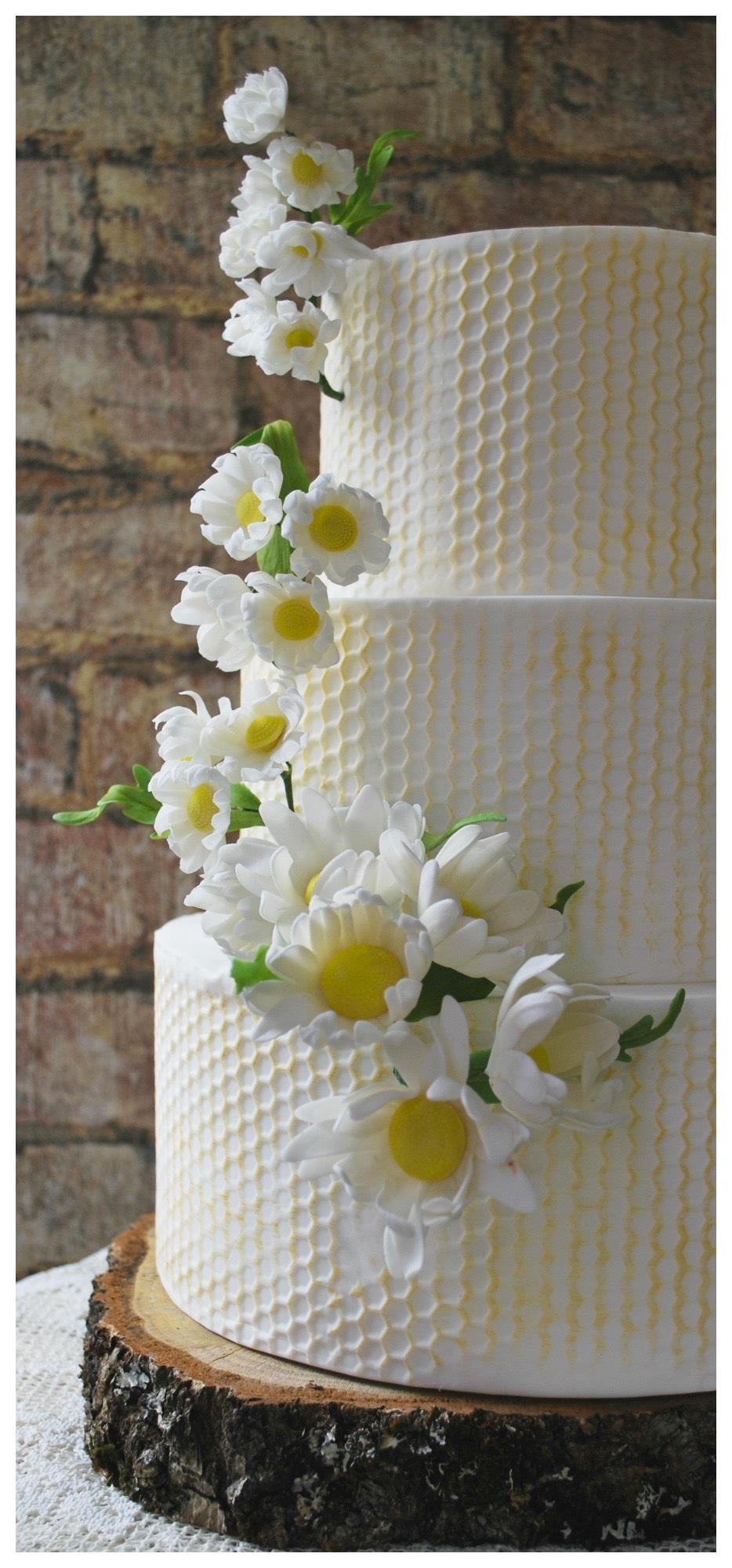 White textured  fondant wedding cake with yellow honeycomb patterned wedding