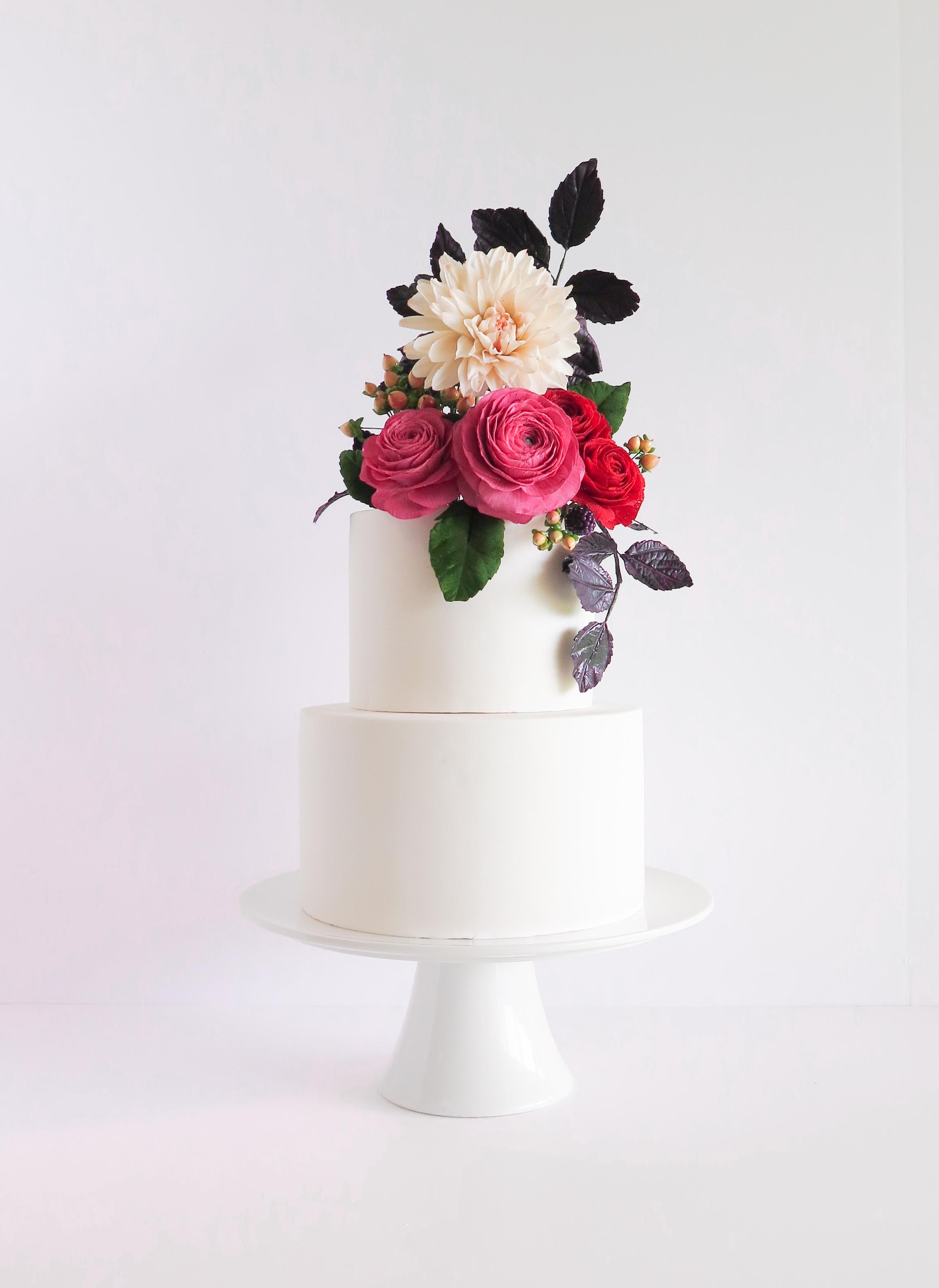 White wedding with pink sugar flower bouquet on top
