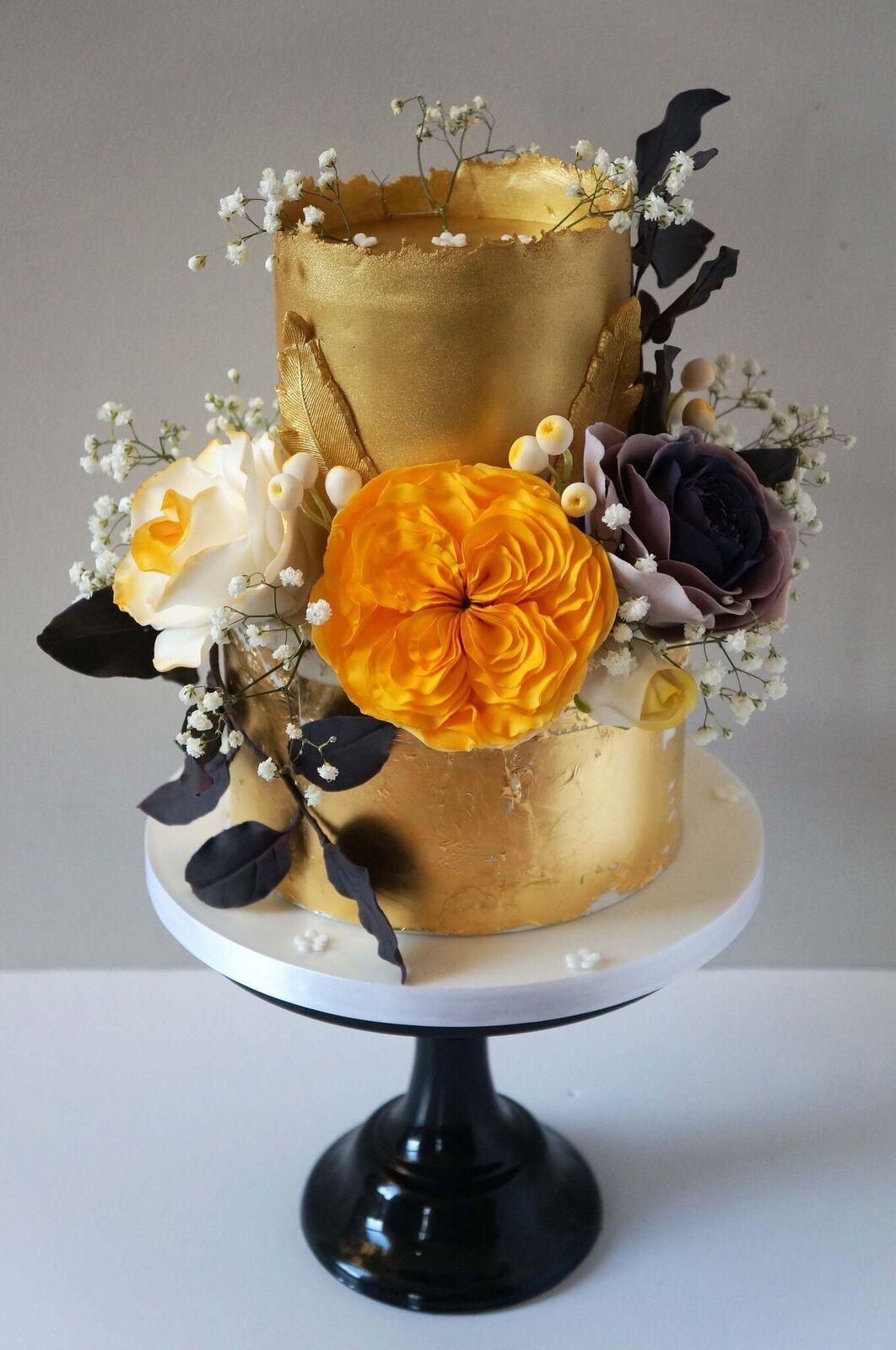 Gold fondant wedding cake with orange flowers