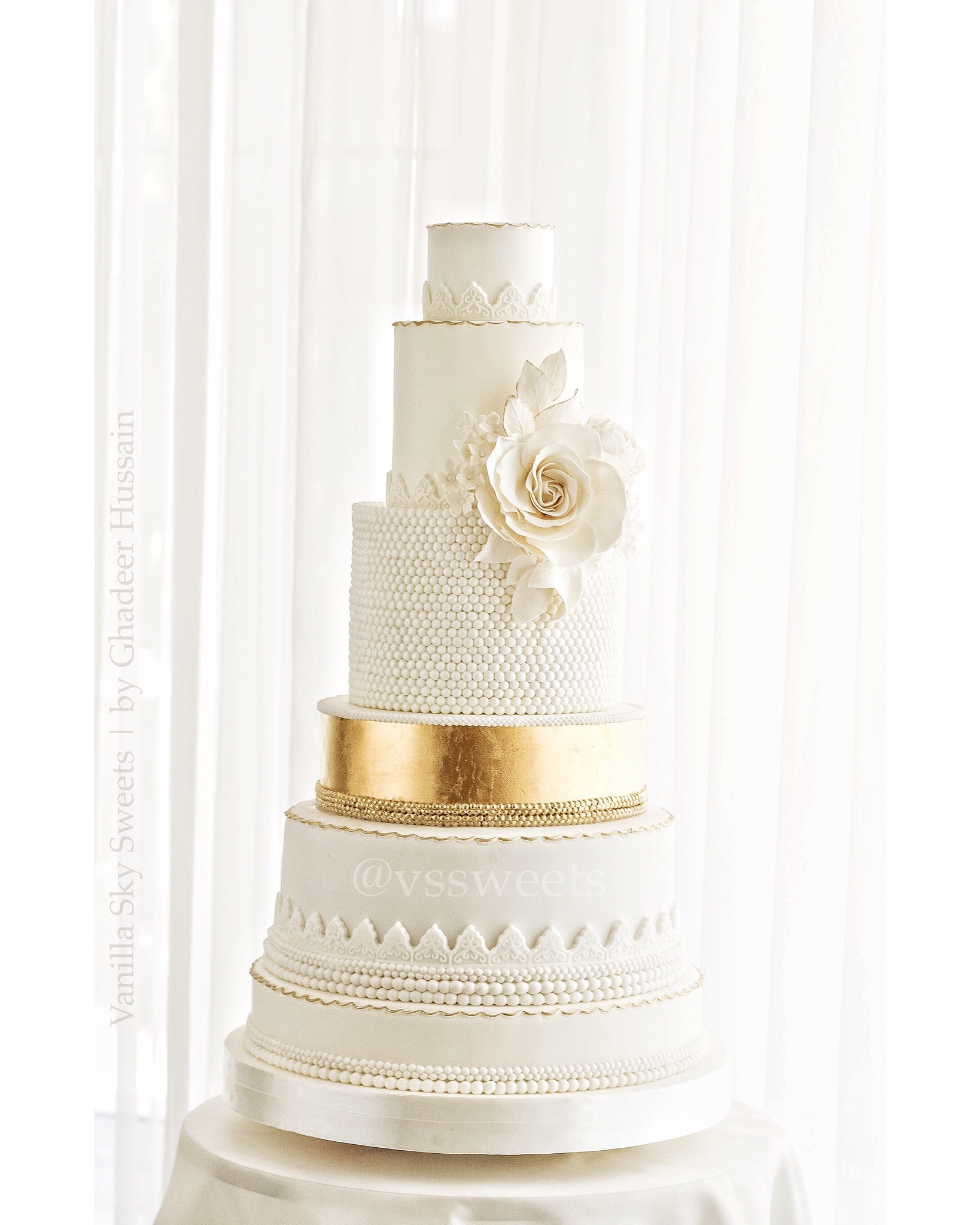 White fondant wedding cake with gold tier