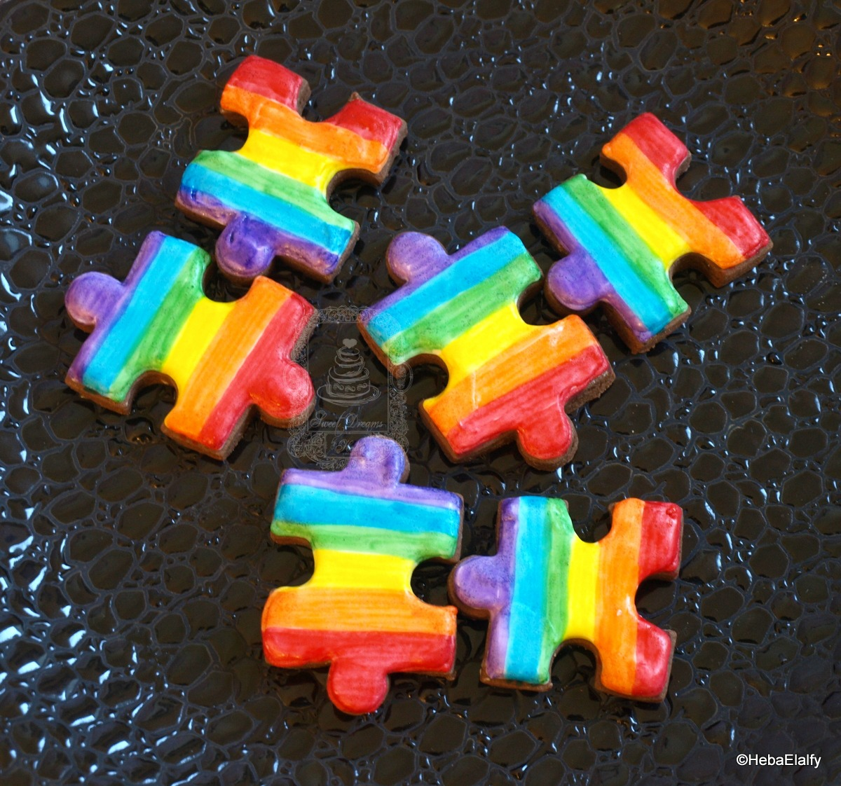 Rainbow colored puzzle piece fondant cookies
