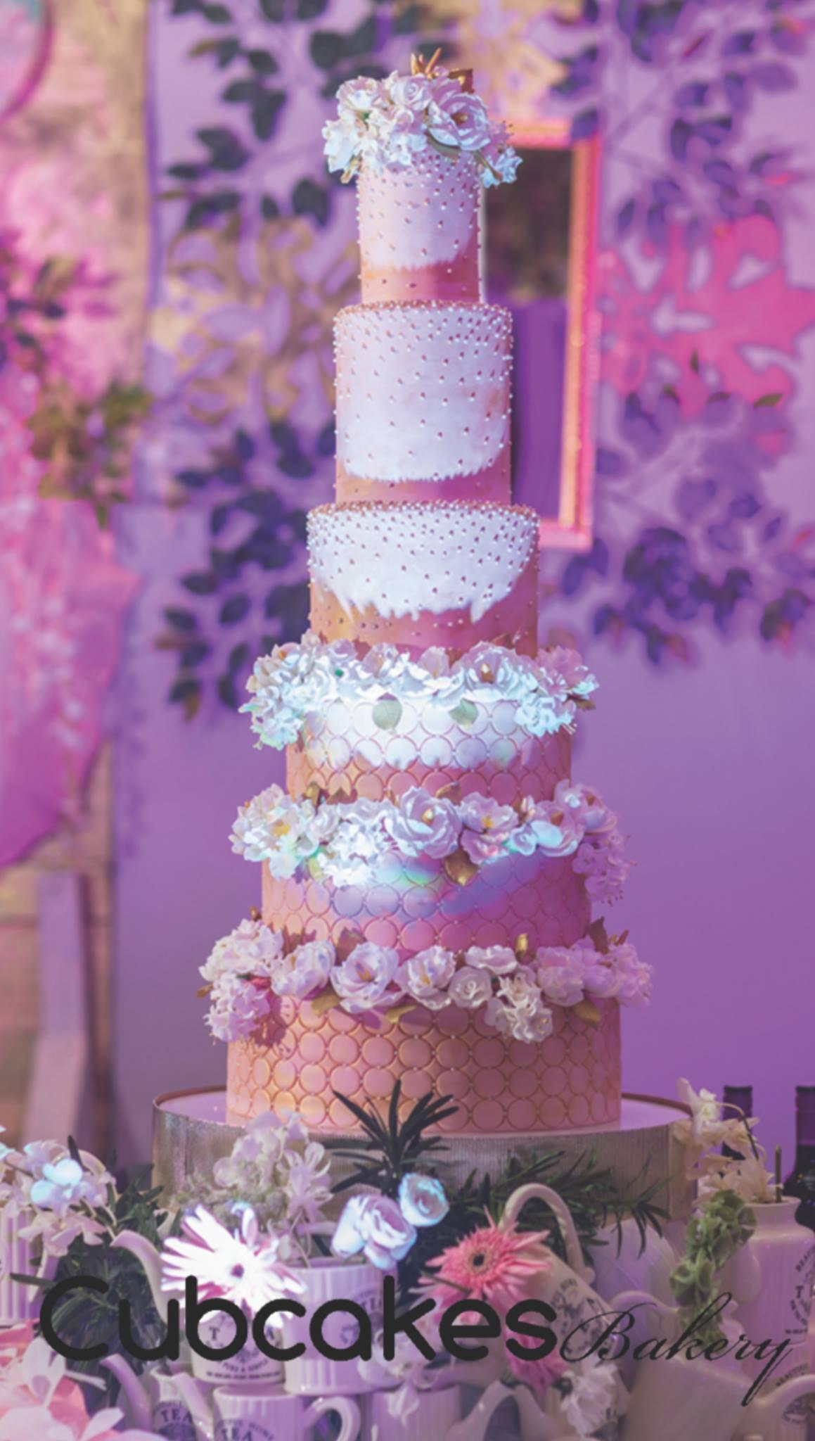 Peach and white tall wedding cake with white sugar flowers