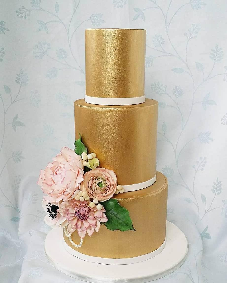 All gold wedding cake with light pink sugar flowers