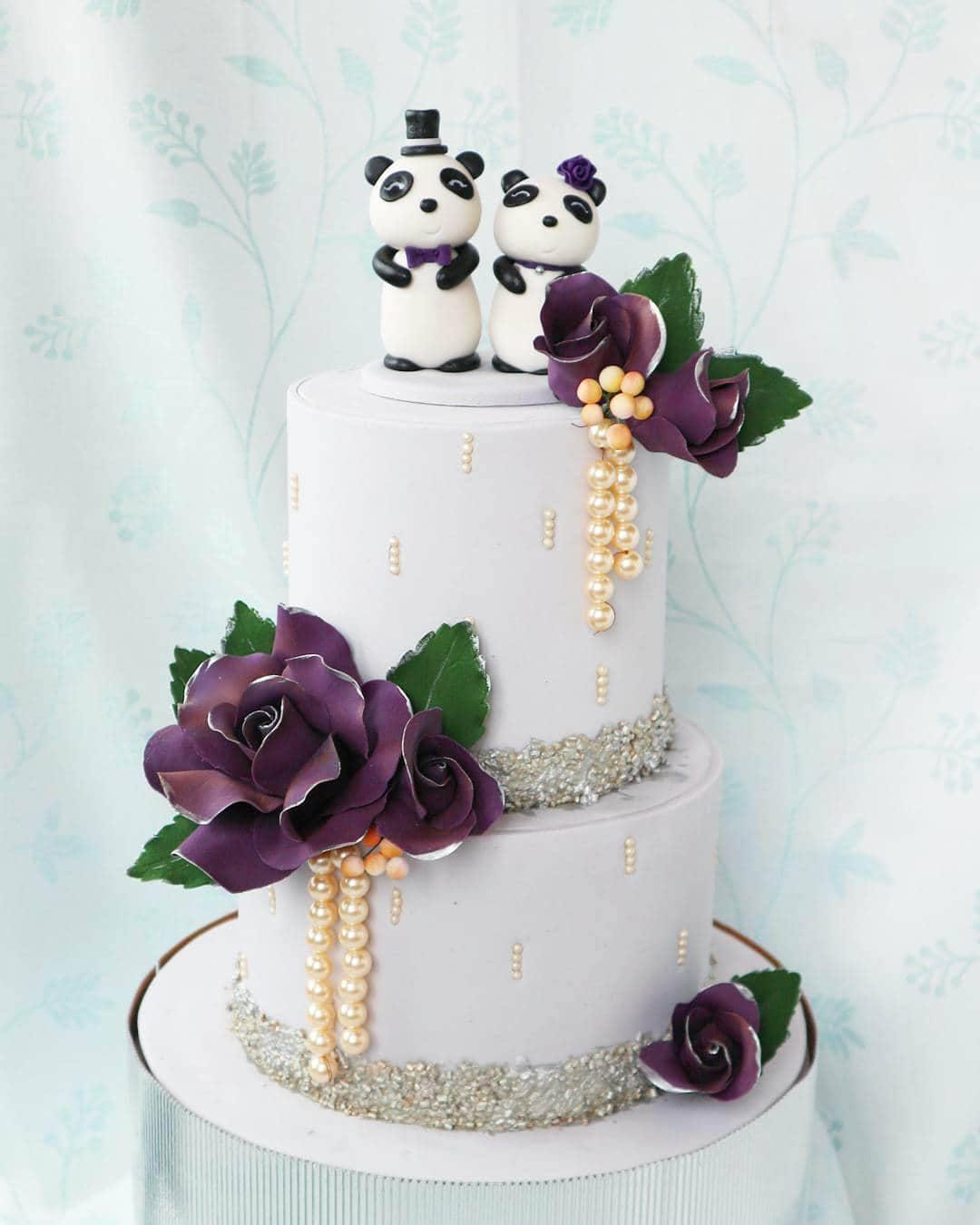 White wedding cake with dark purple sugar flowers