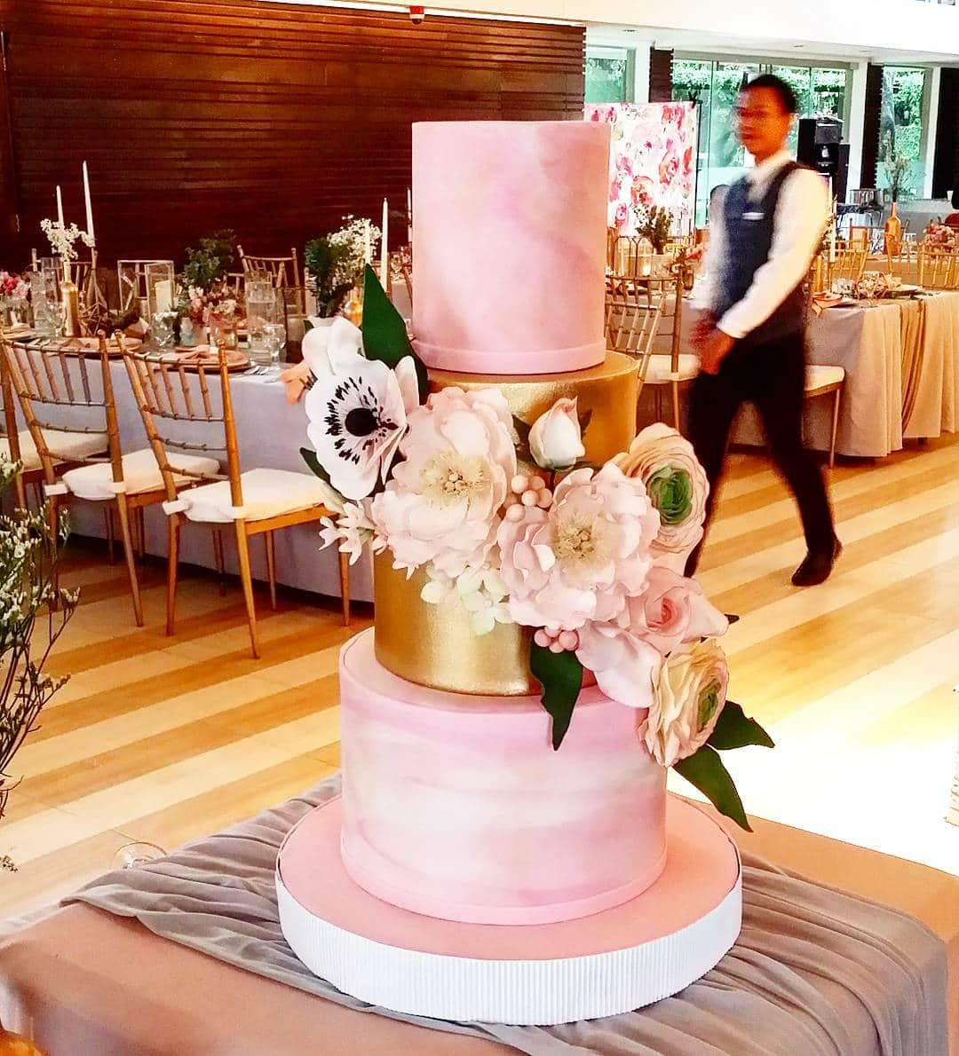 Pink marbled wedding cake with gold