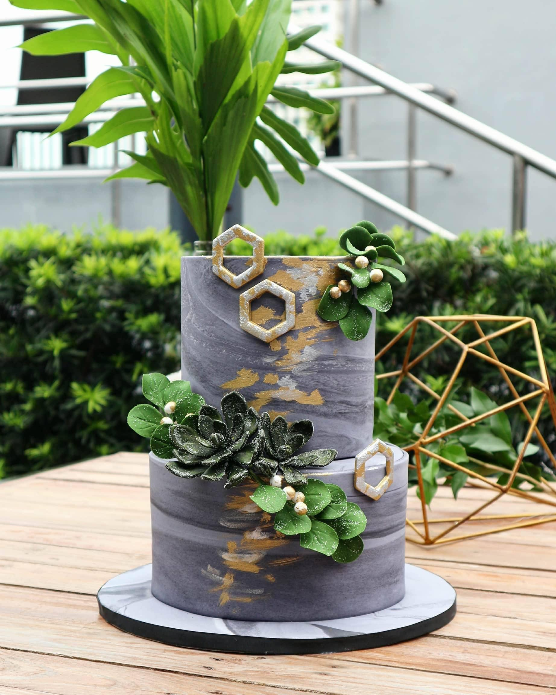 Gray marbled wedding cake with green succulents