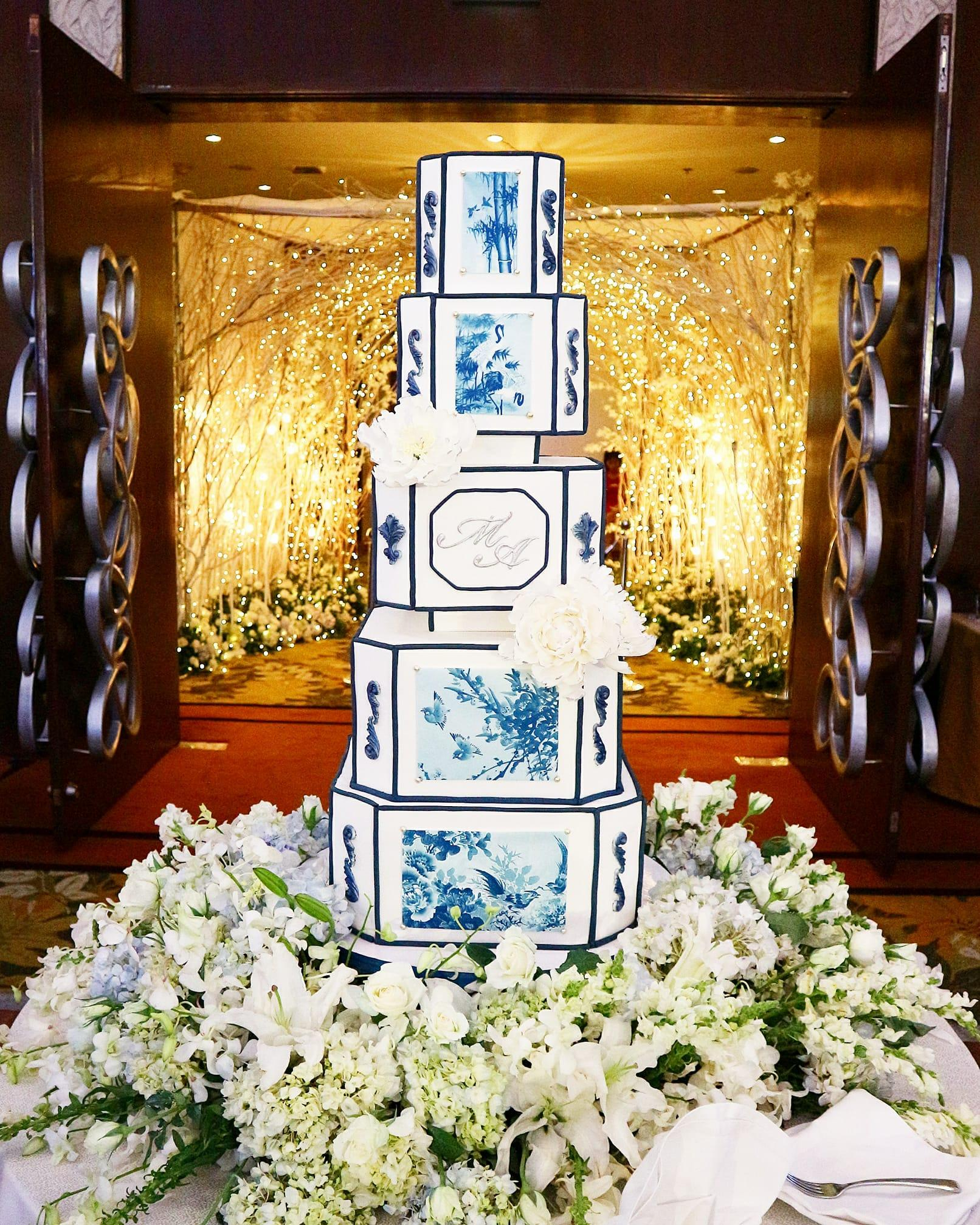 White wedding cake with hand painted blue landscapes