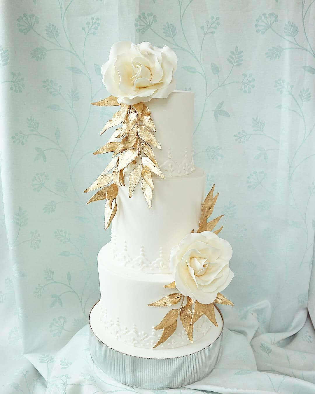 All white wedding cake with gold leaves