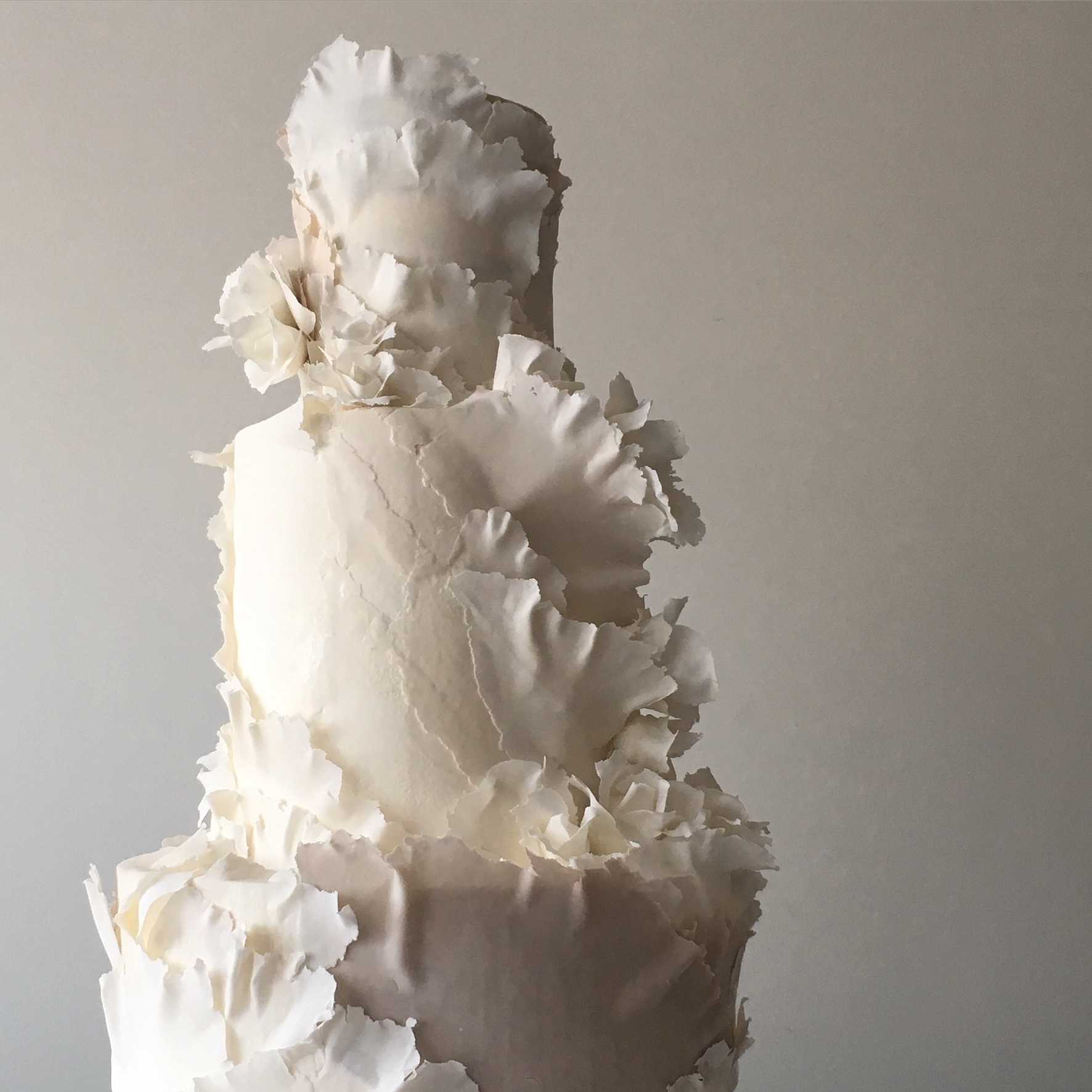 Ivory and white wedding cake with frill ruffles