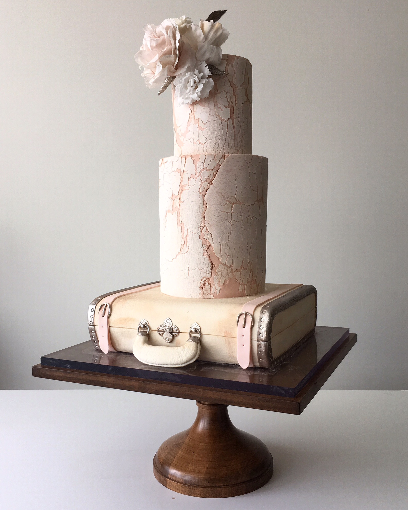 Ivory textured wedding cake on suitcase