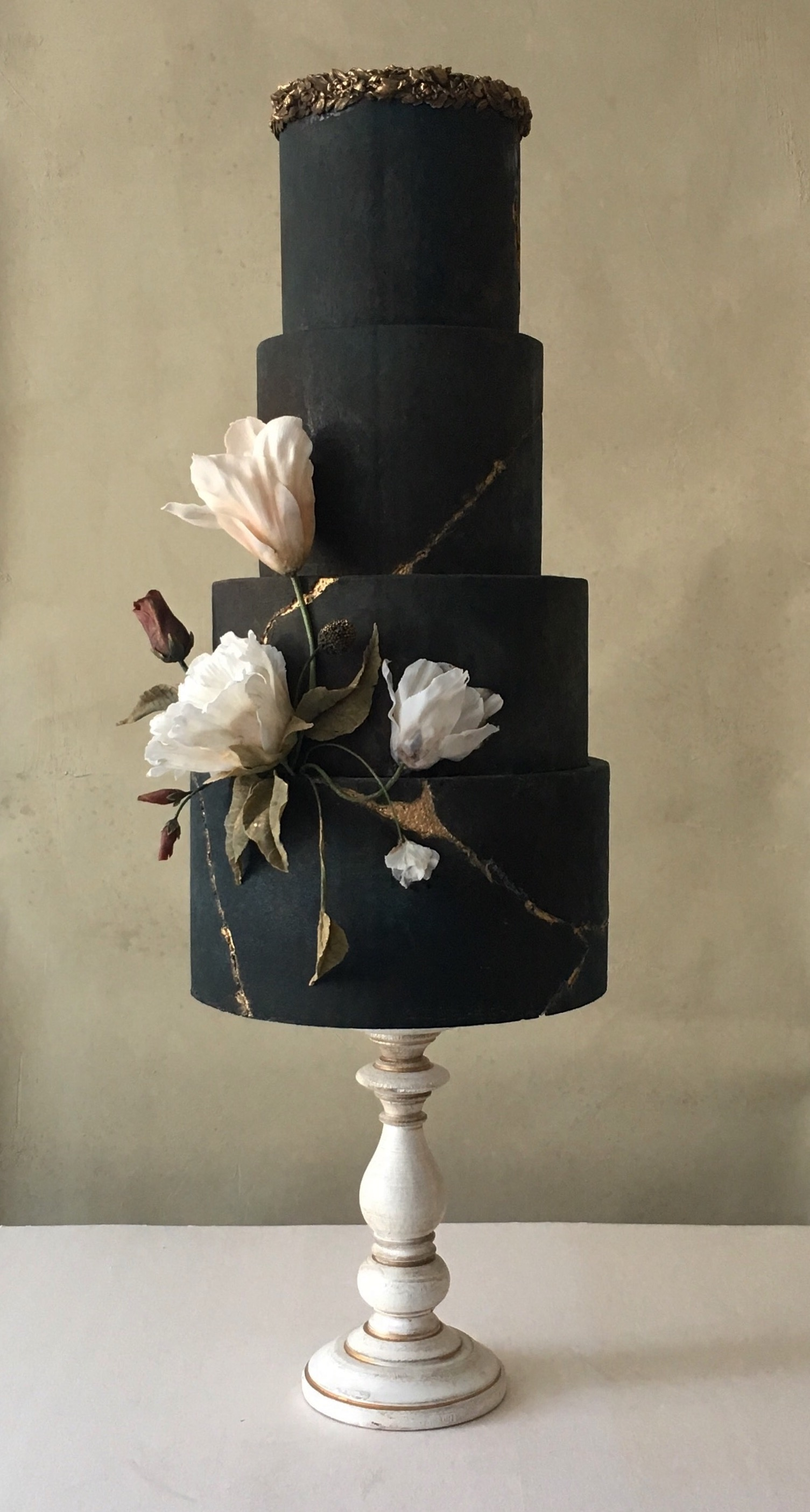 All black cake with center sugar flower stems