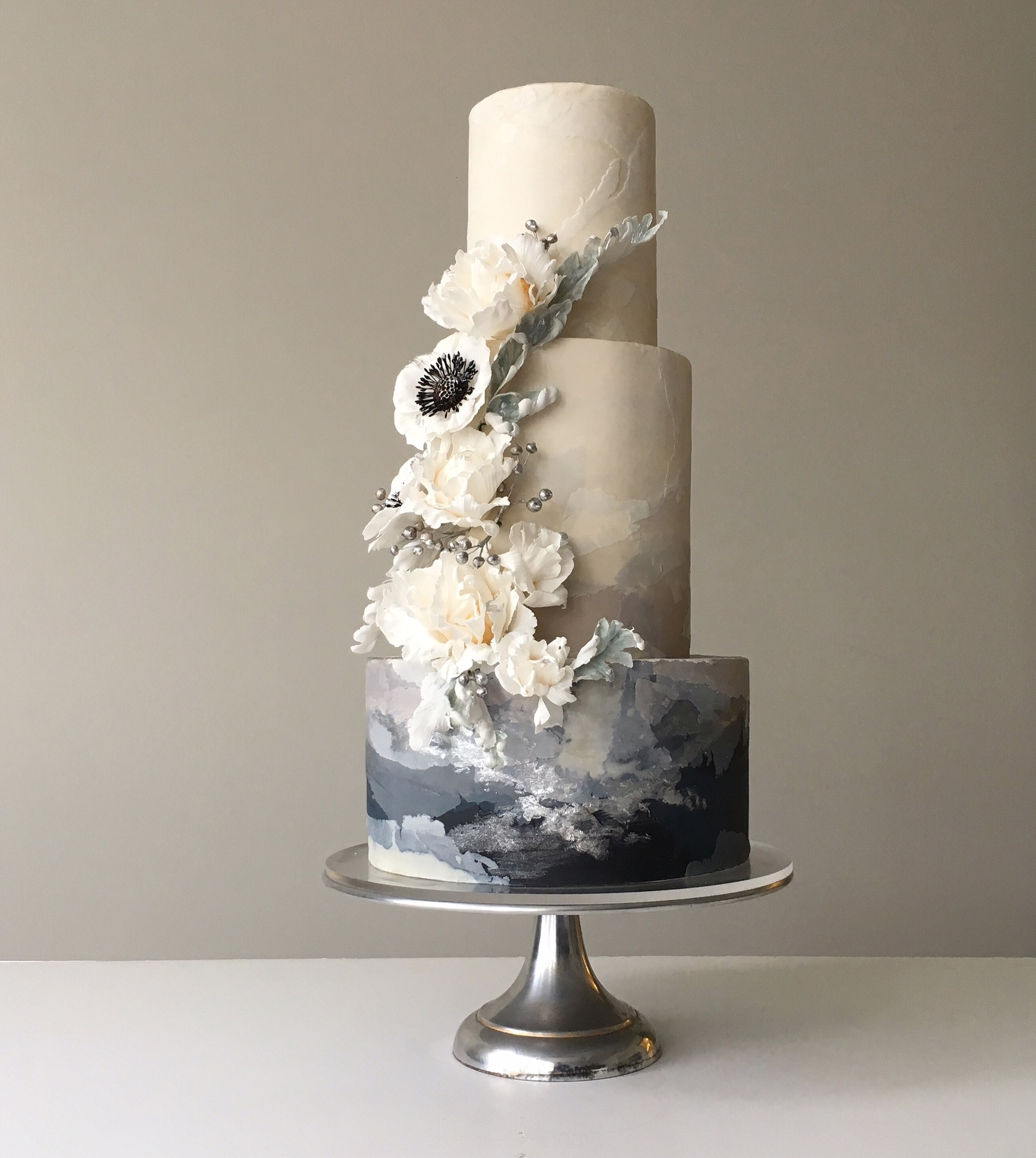 White wedding cake with handprinted ombre gray with anemone sugar flowers