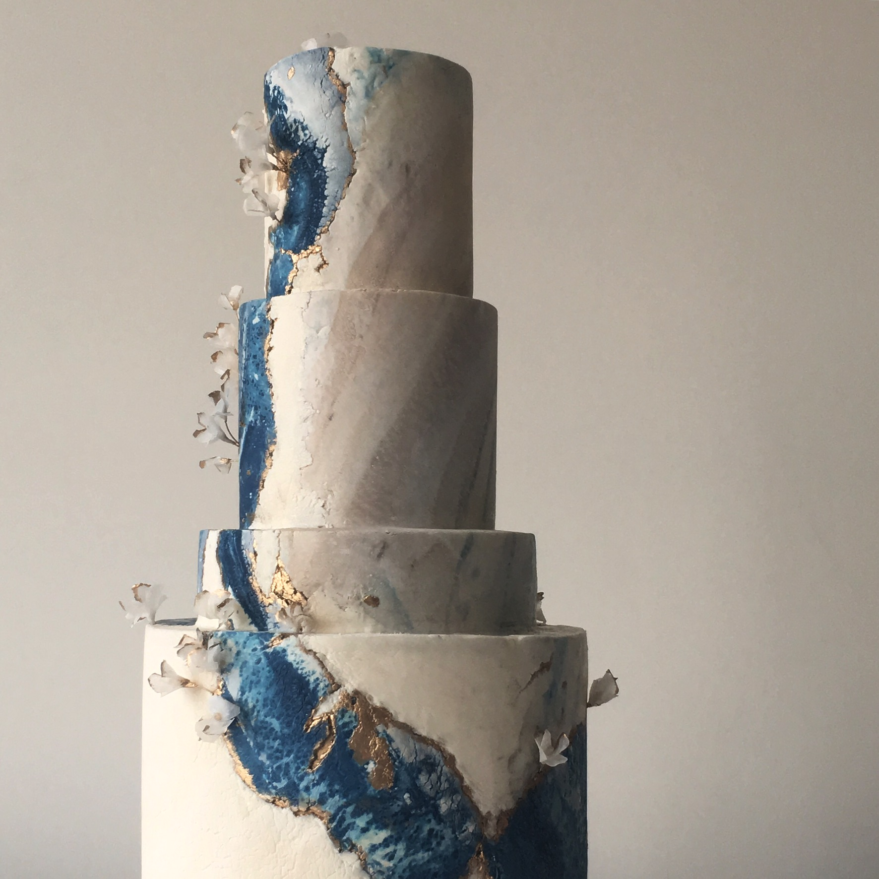 Gray marbled wedding cake with blue crackle and gold leaf