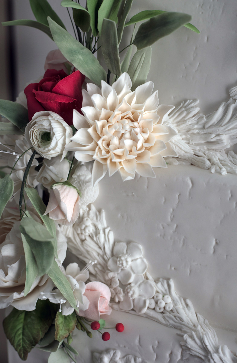 White bas relief textured cake with sugar flowers