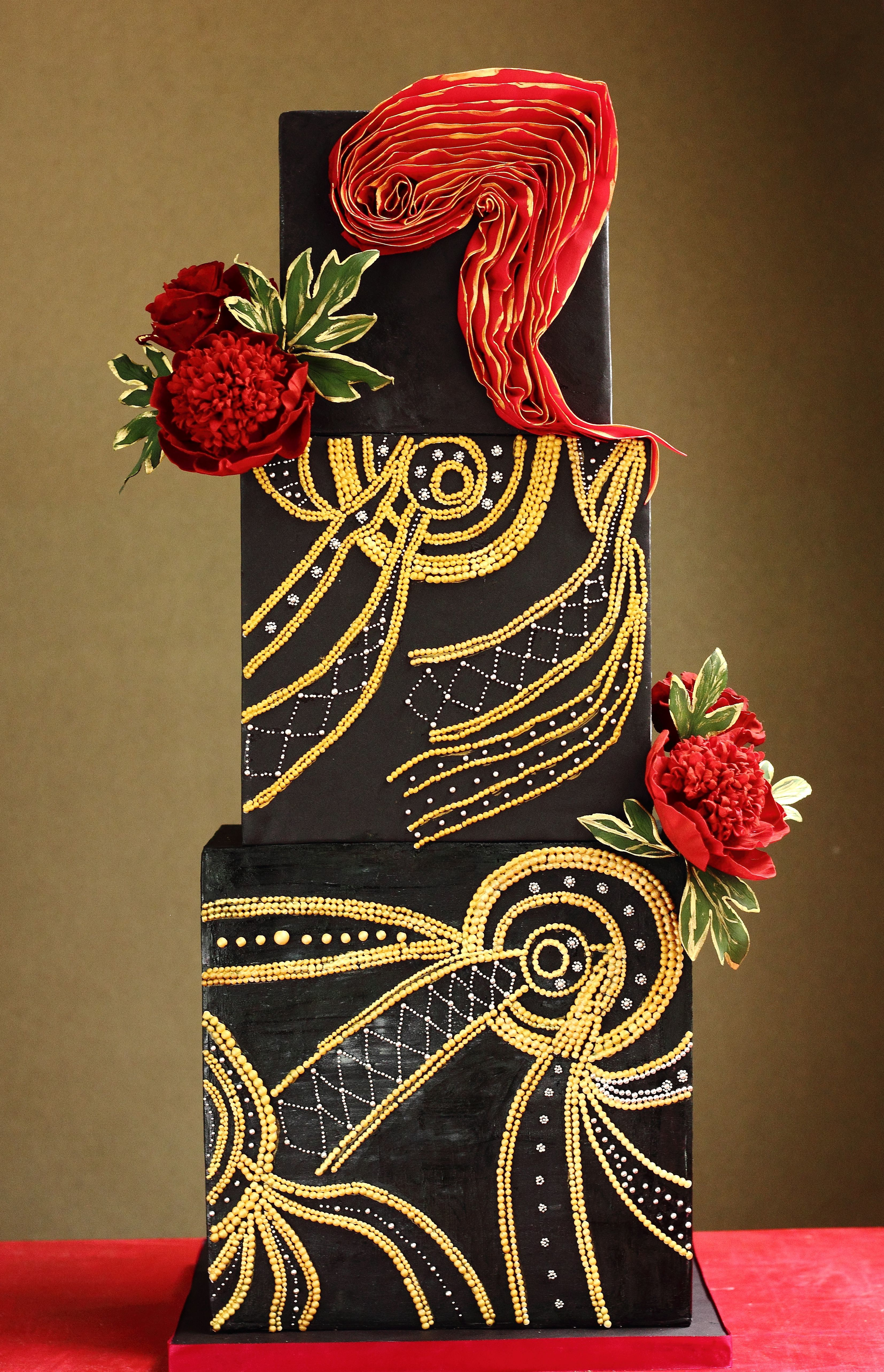 Black and gold square wedding cake with red accents