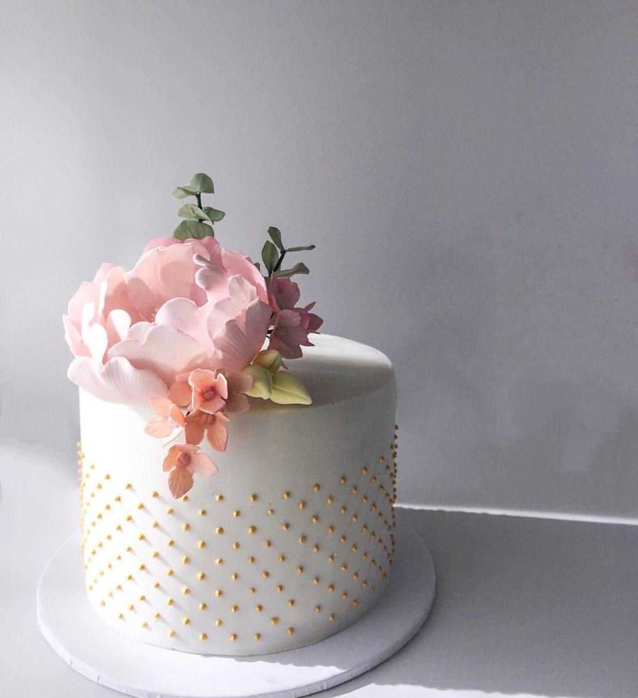 White mini wedding cake with pink sugar flower