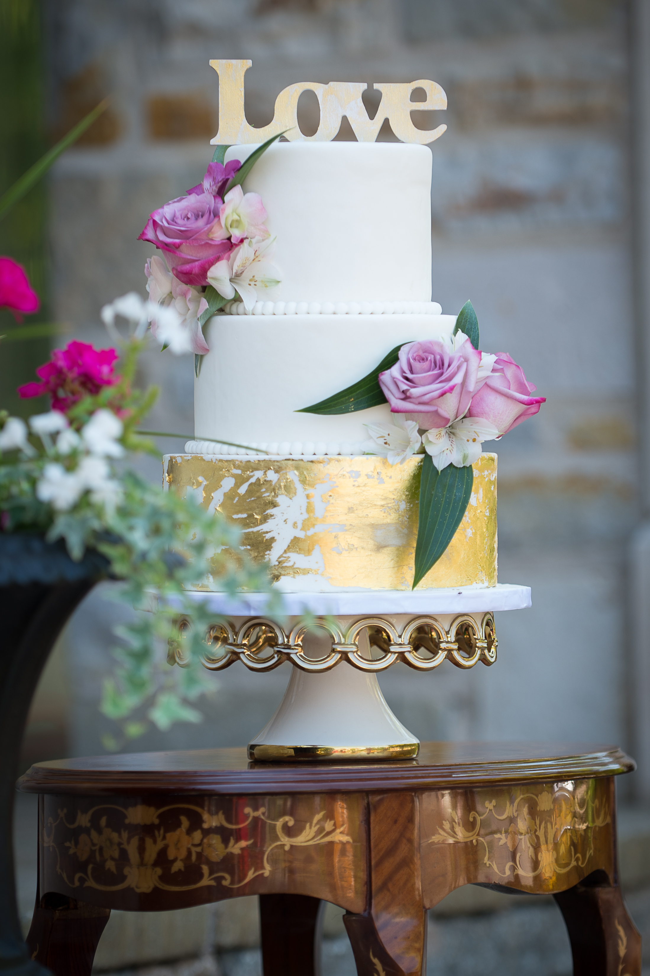 White and gold wedding cake with pink sugar flowers