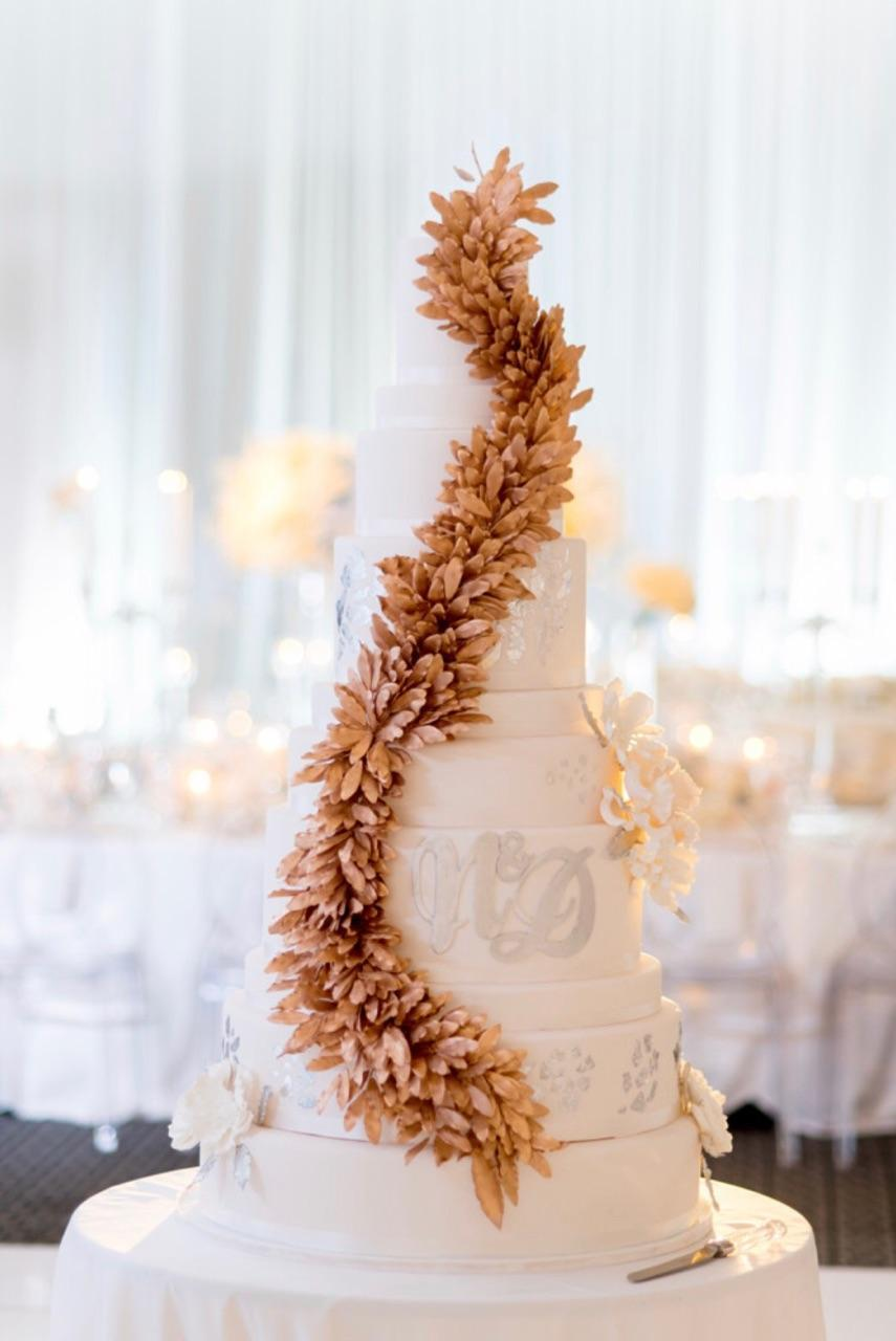 White fondant wedding cake with cascading copper sugar leaves