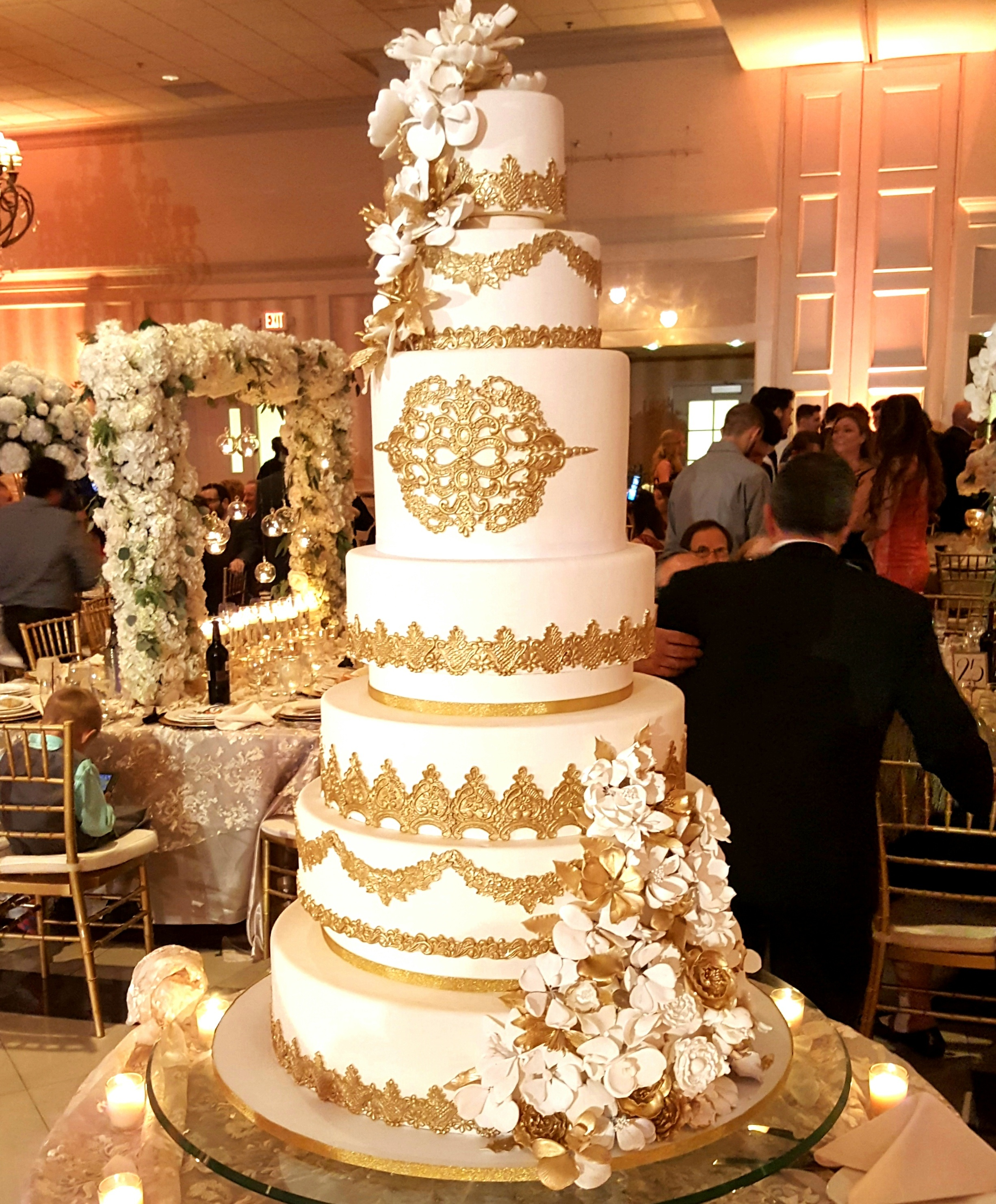 Vintage white wedding cake with gold accents and sugar flowers