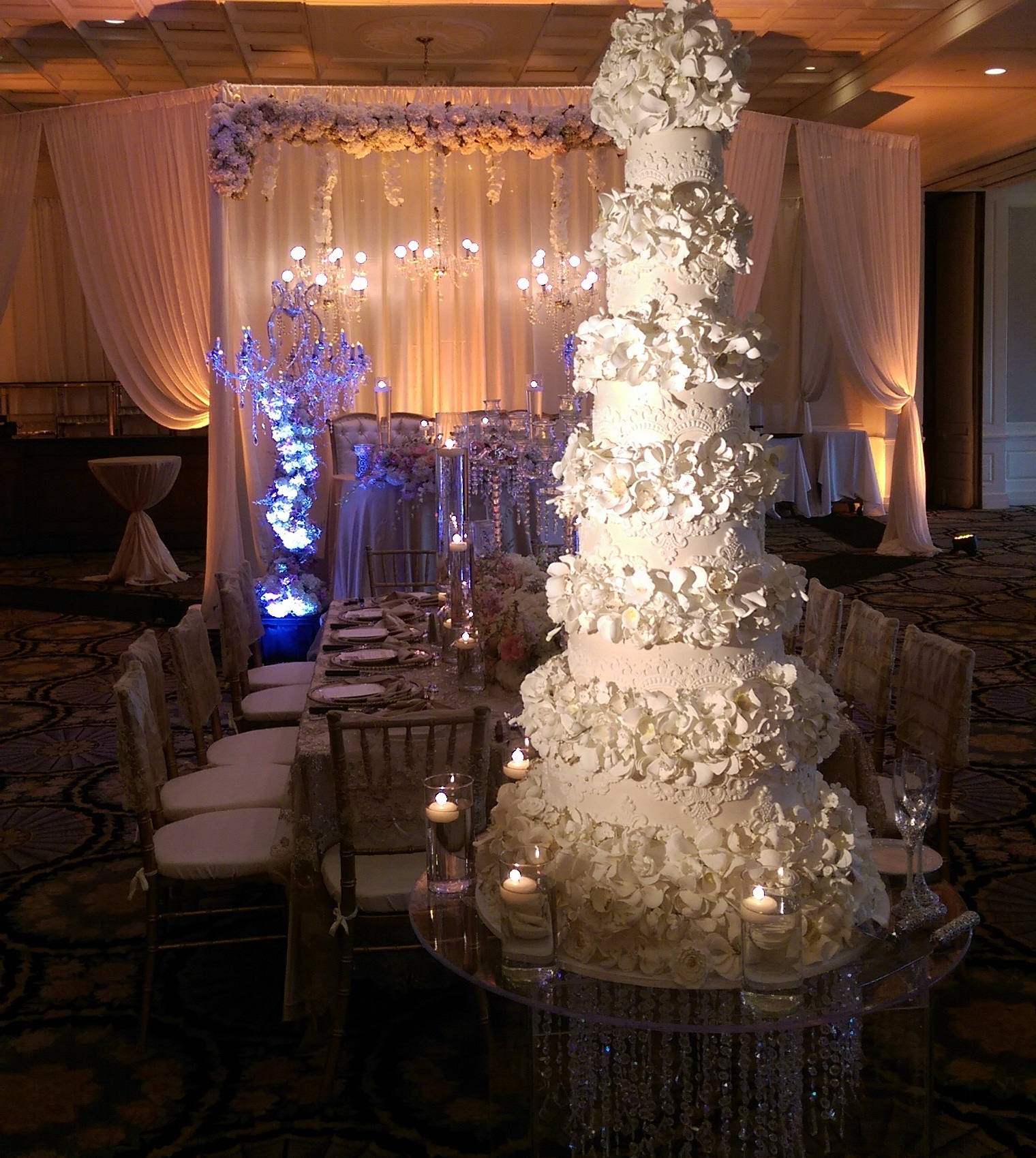 Tall white wedding cake with white sugar flowers