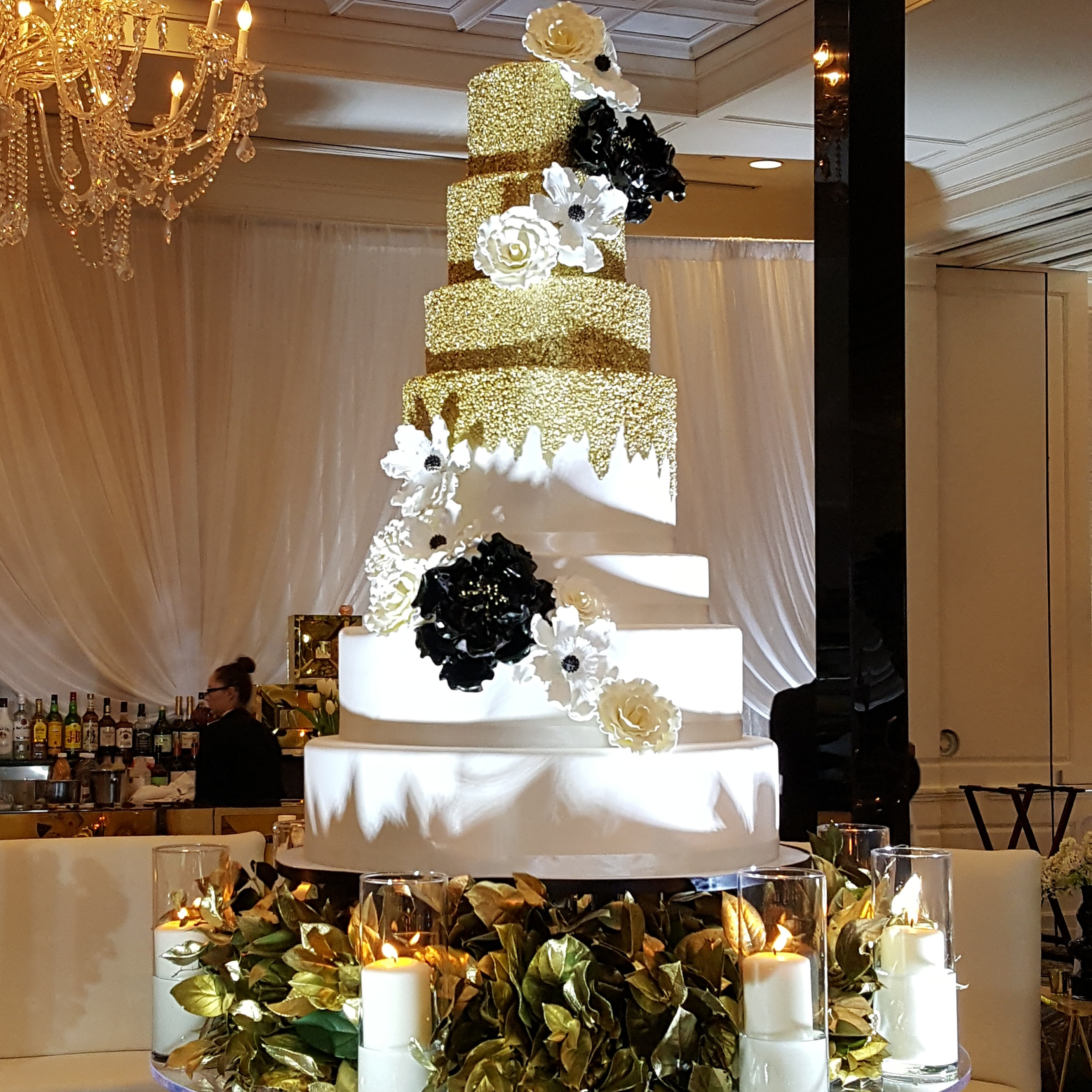 White wedding cake with gold sparkle and black and white sugar flowers