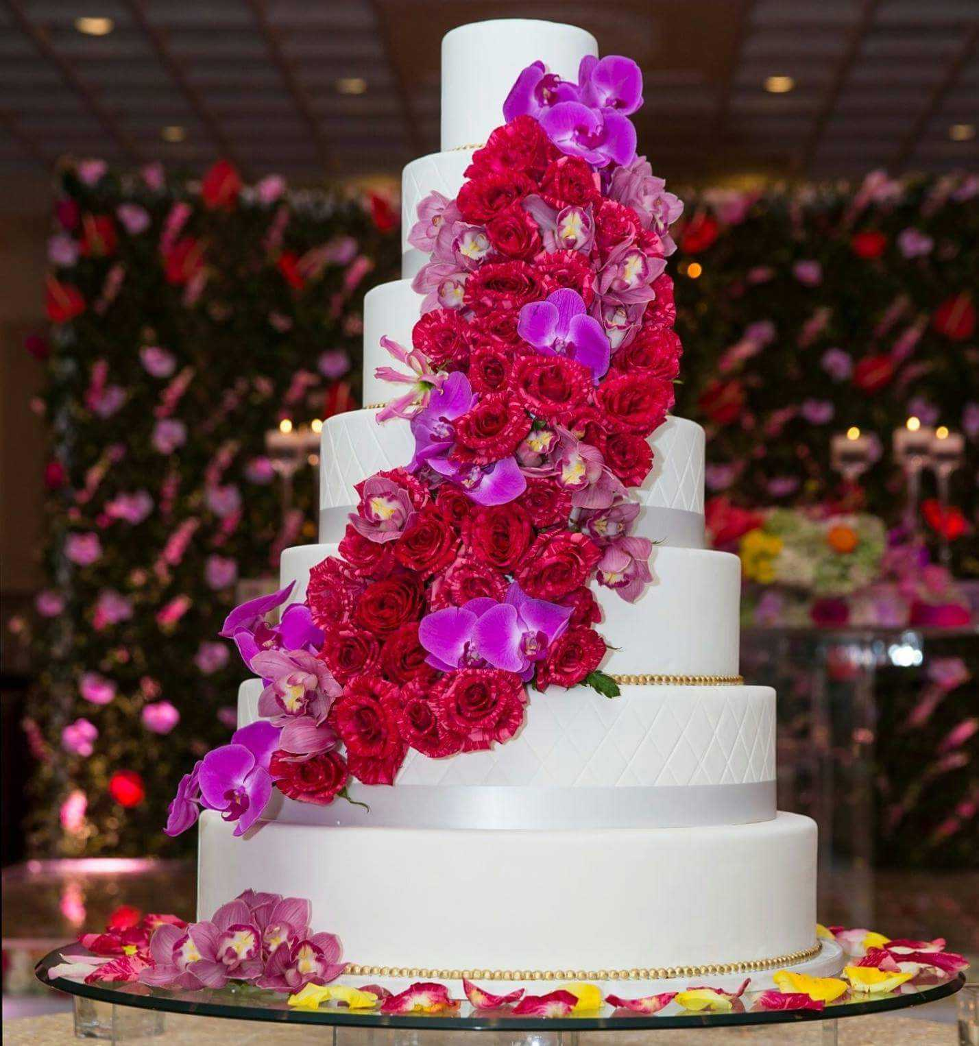 White wedding cake with pink and red cascading sugar roses
