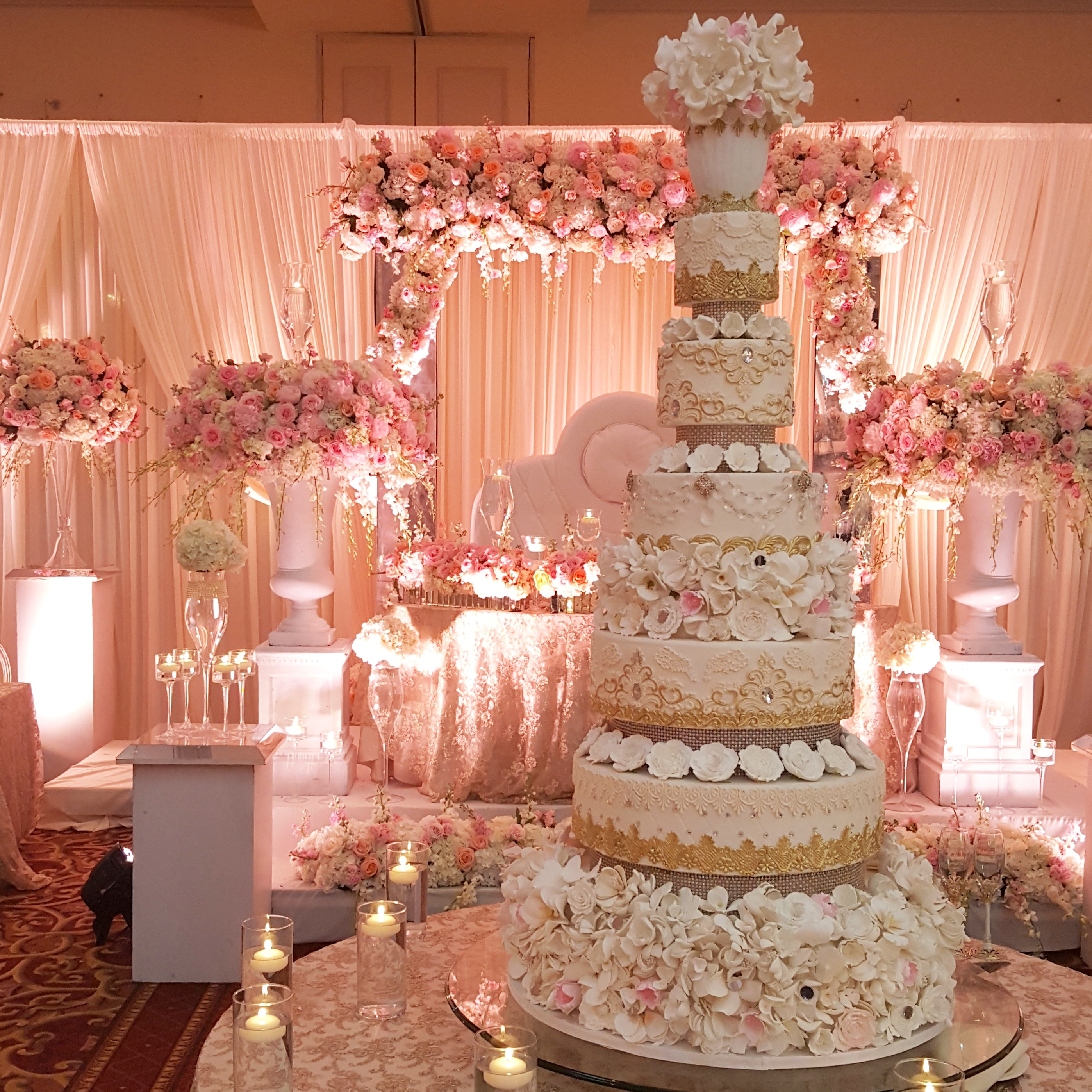 Light pink wedding cake with gold accents and sugar flowers