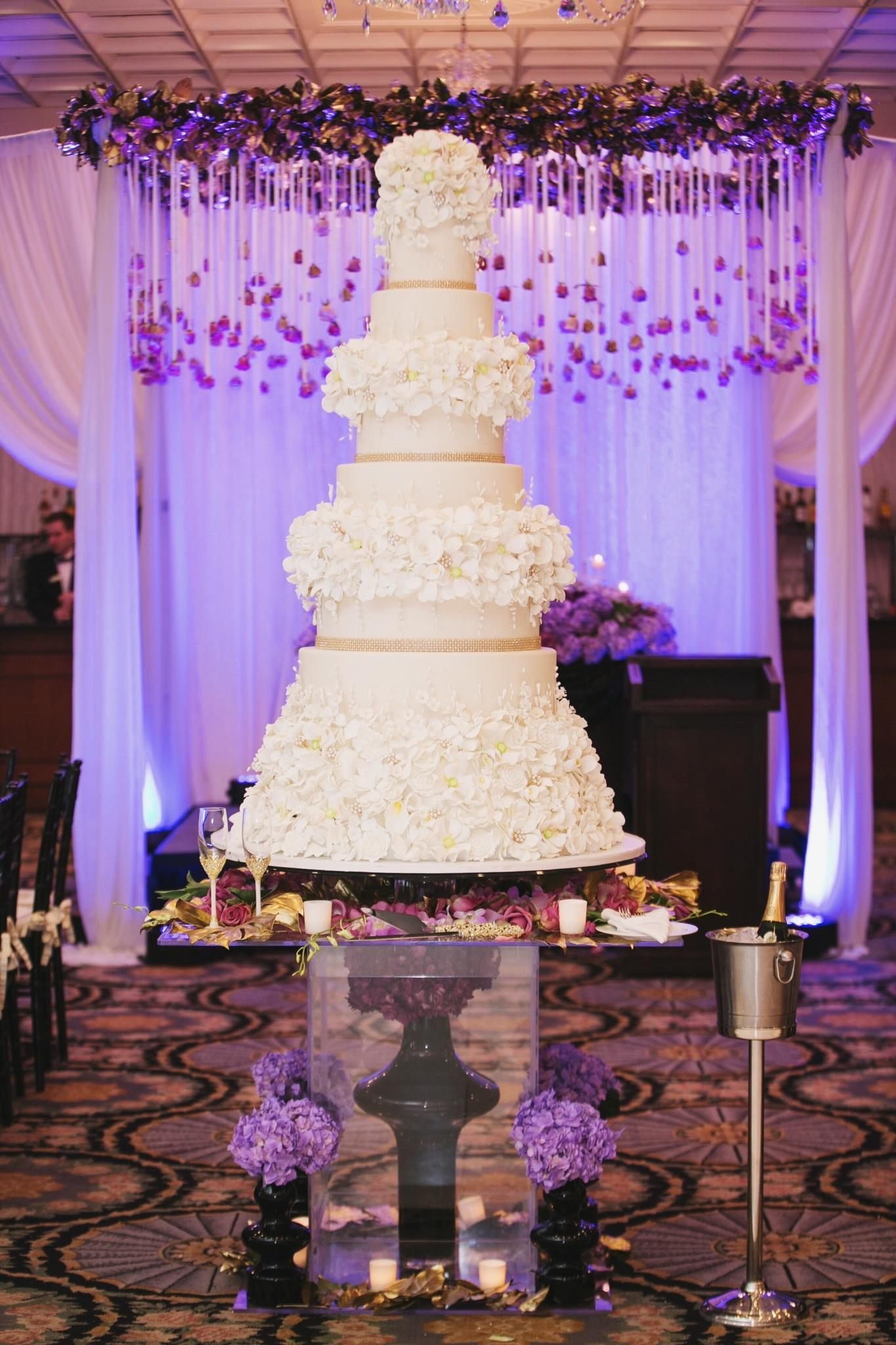 White wedding cake with multiple layers of sugar flowers
