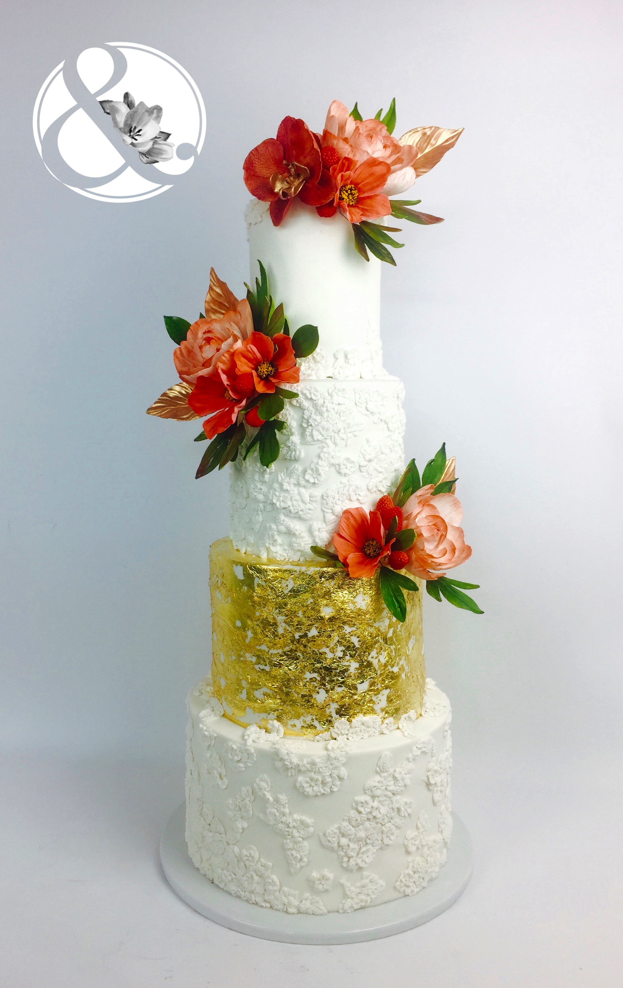 White and gold wedding cake with  red sugar flowers