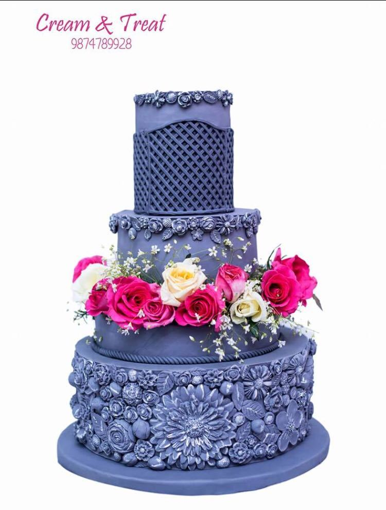 All blue textured fondant wedding cake with bright pink sugar flowers