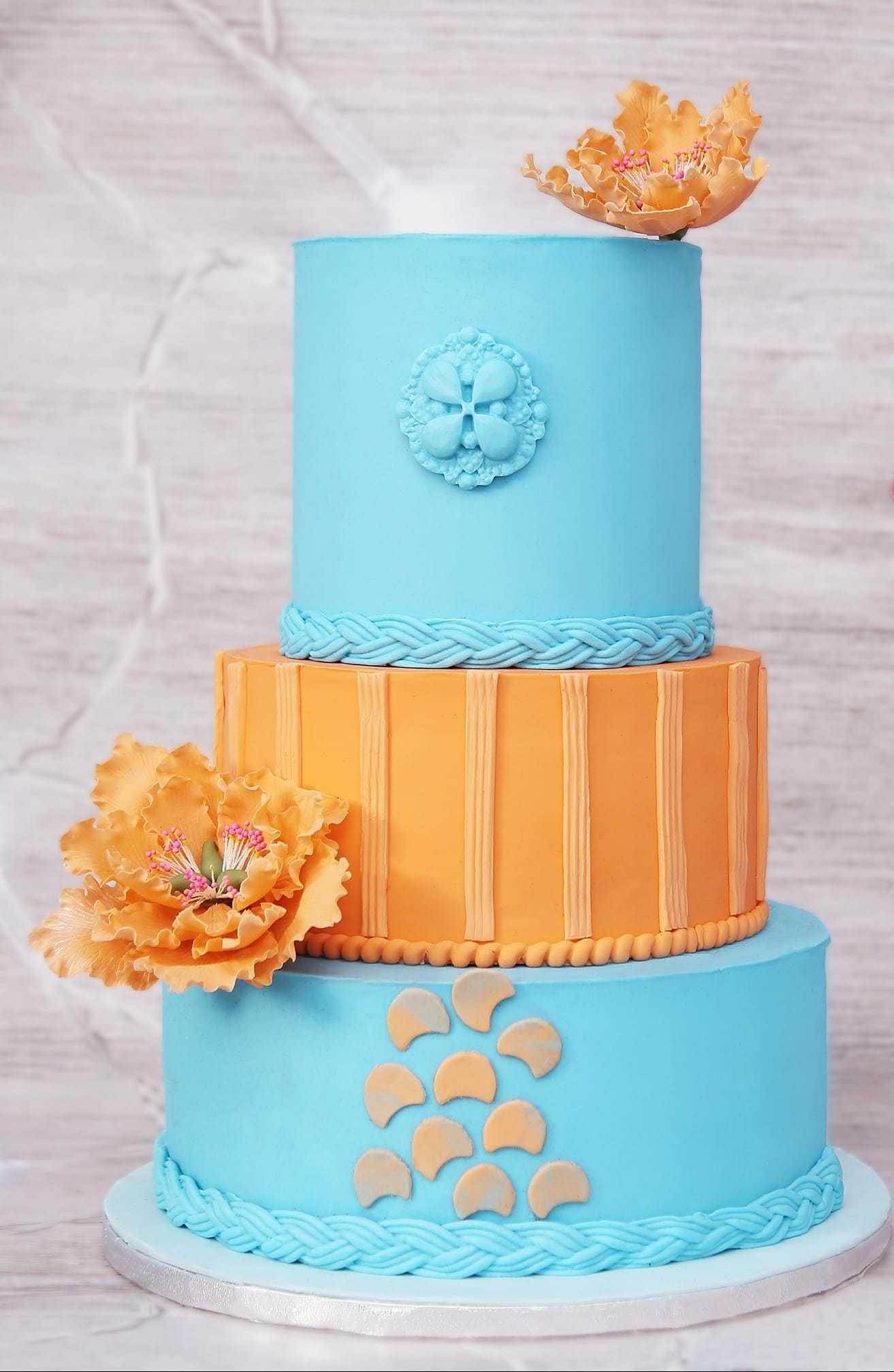 Light blue and orange fondant wedding cake with orange sugar flowers