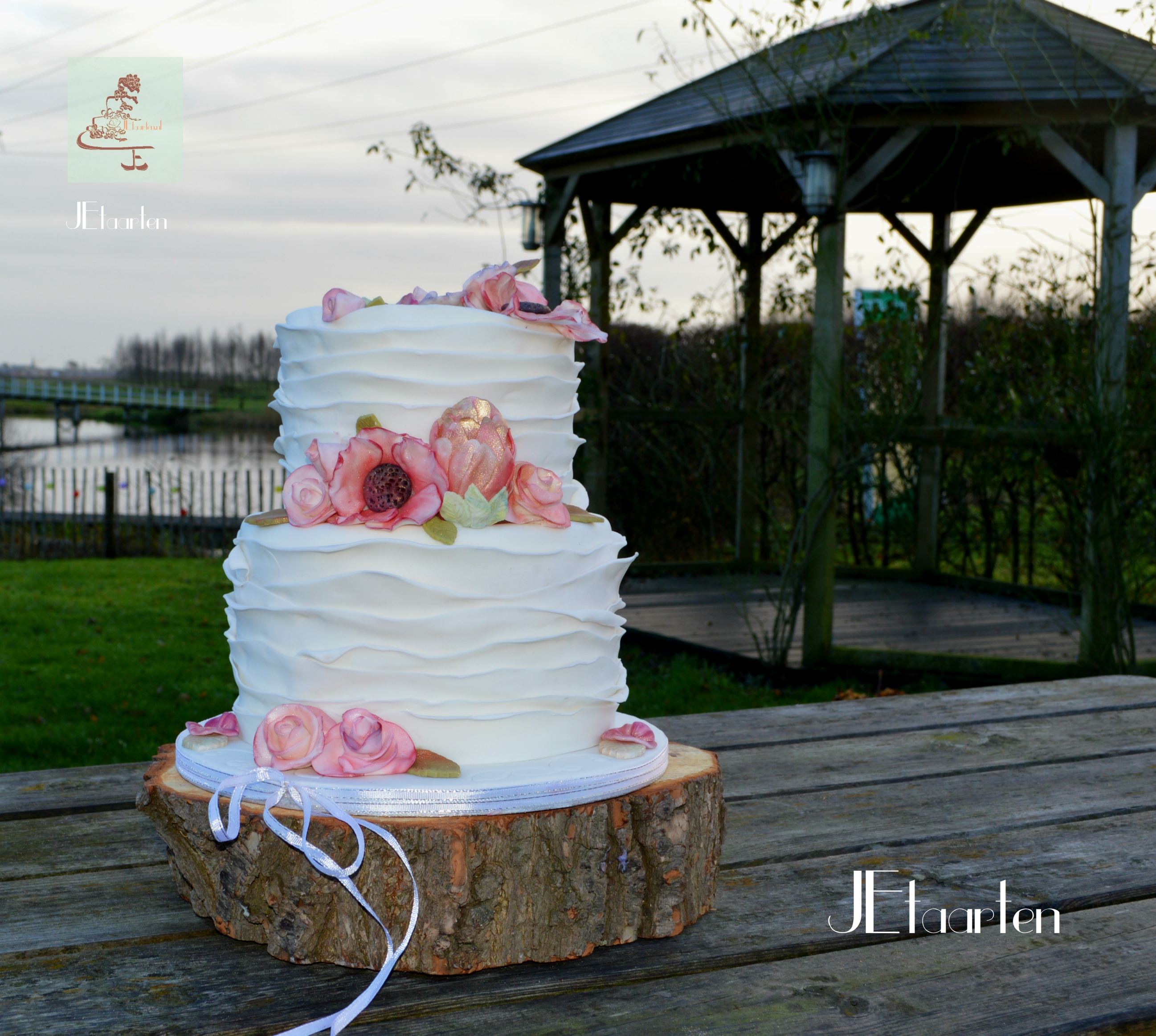 White ruffled wedding cake with pink sugar flowers