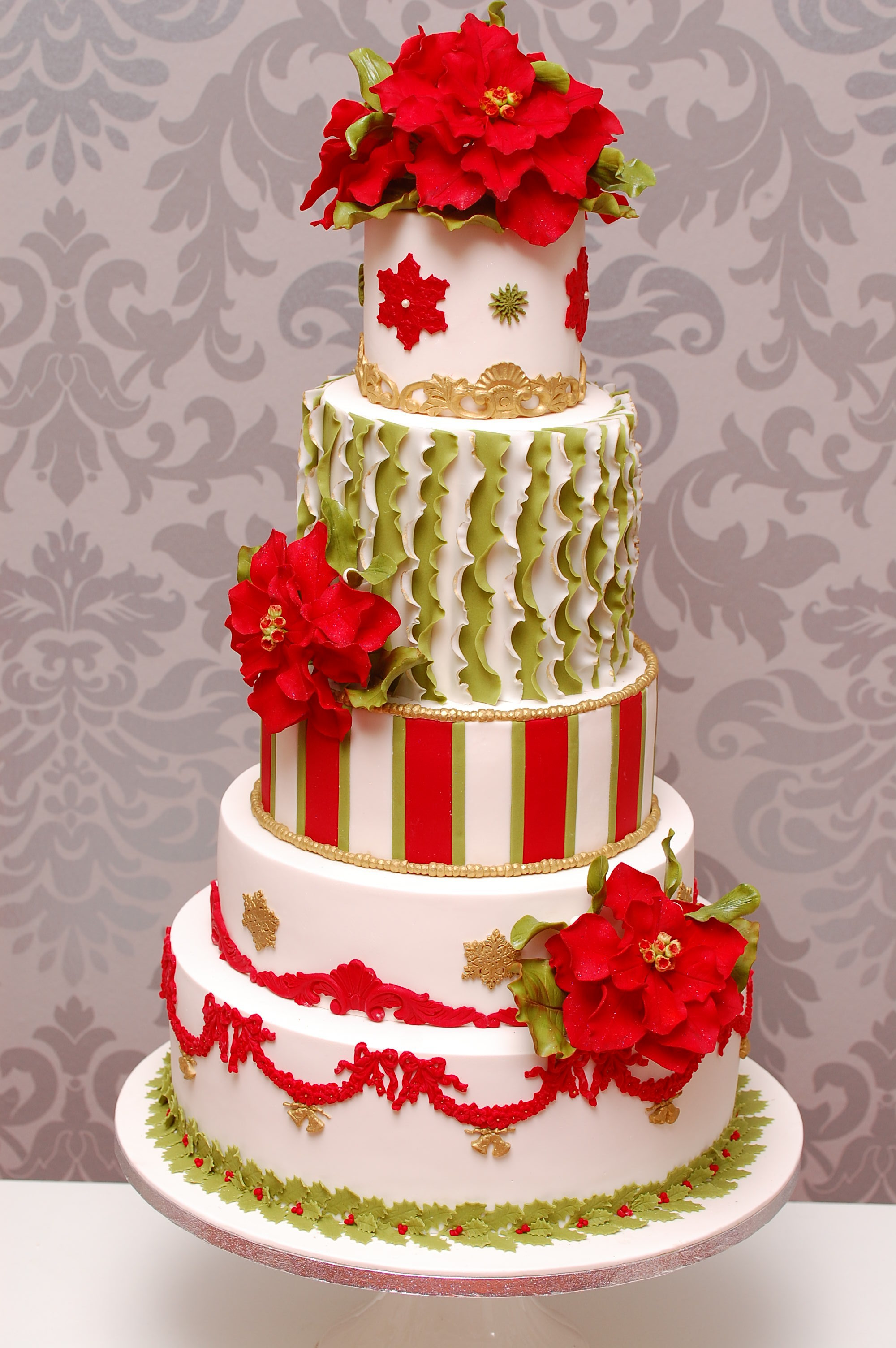 Gold and white fondant wedding cake with red sugar flowers