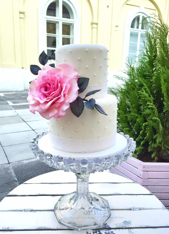 Ivory wedding cake with big pink sugar rose
