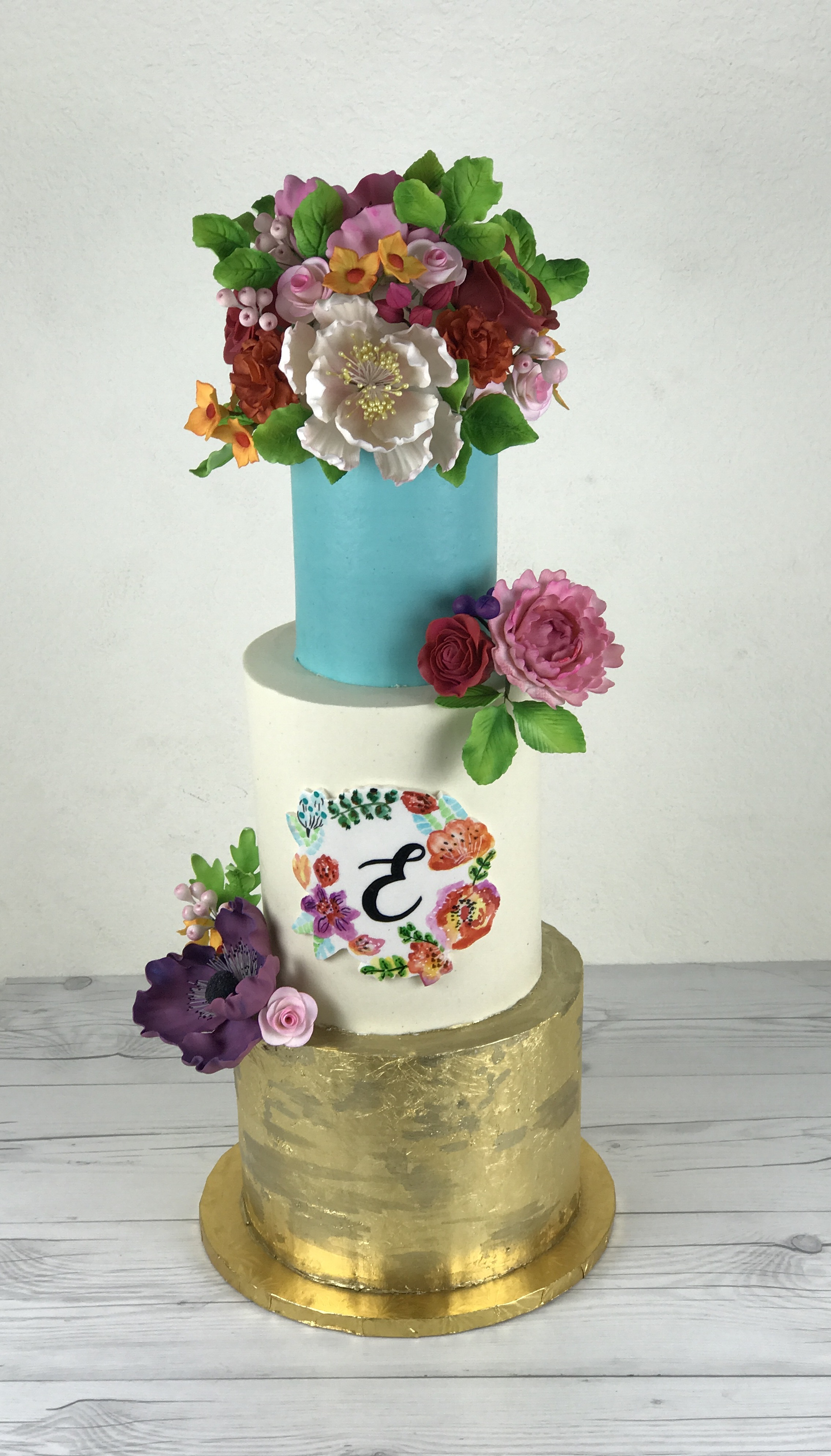 Bright blue and gold monogramed wedding cake with sugar flower bouquet