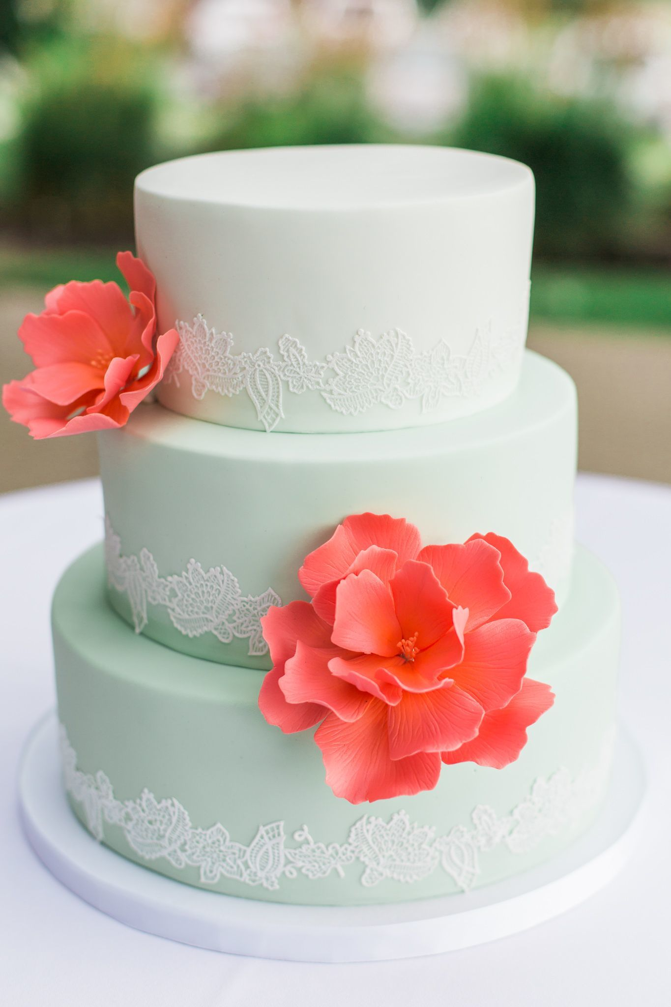 Pastel green fondant wedding cake with coral sugar flowers