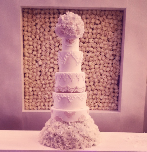 Tall white wedding cake with sugar pearls and flowers